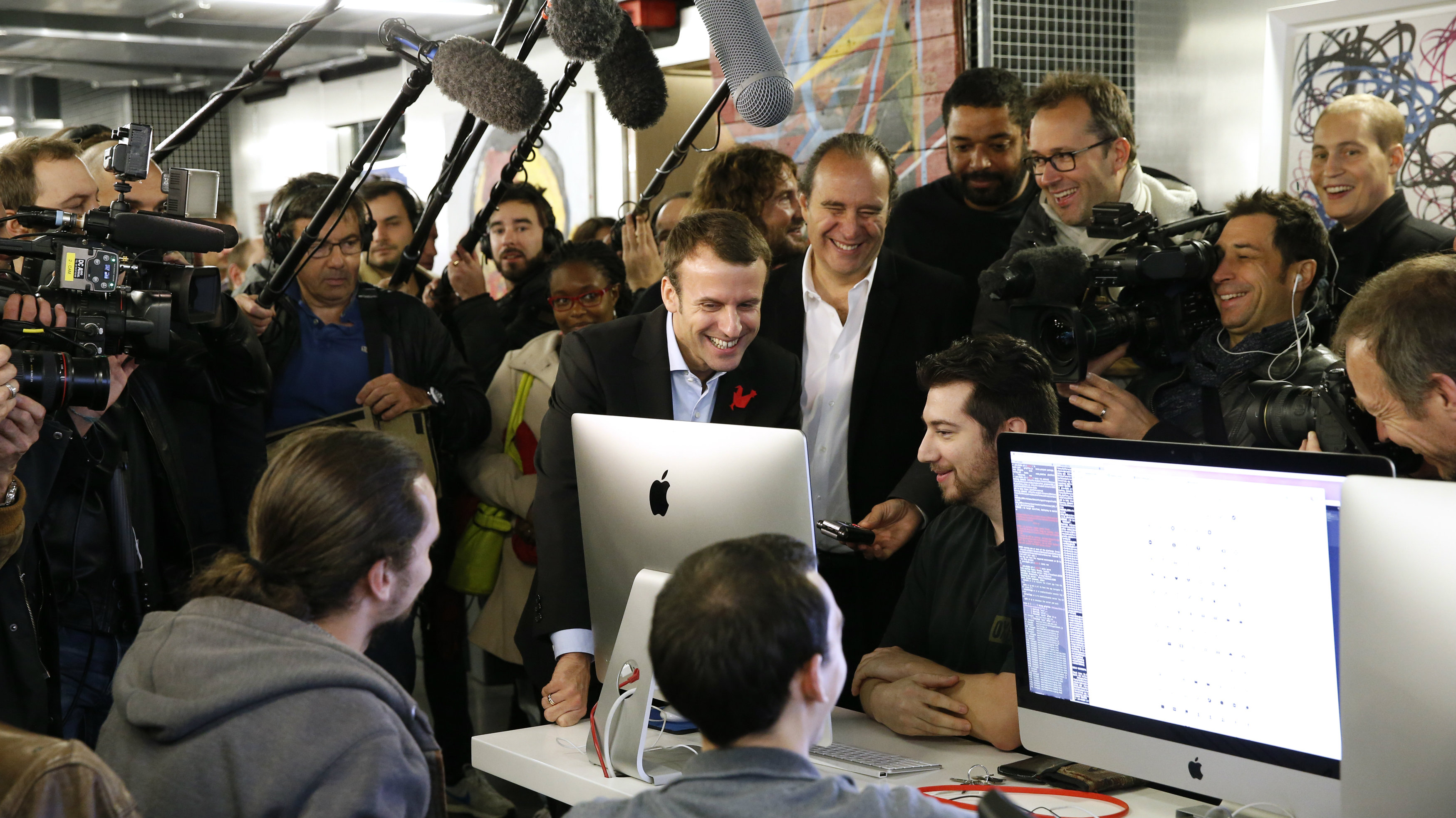 Journalists surround Xavier Niel (C), founder of French broadband Internet provider Iliad, French Economy Minister Emmanuel Macron (L) and Kwame Yamgnane (R) visit the 42 school campus in Paris, France, October 27, 2015. The French school 42, a private French computer programming school, was created and funded by Xavier Niel. REUTERS/Benoit Tessier