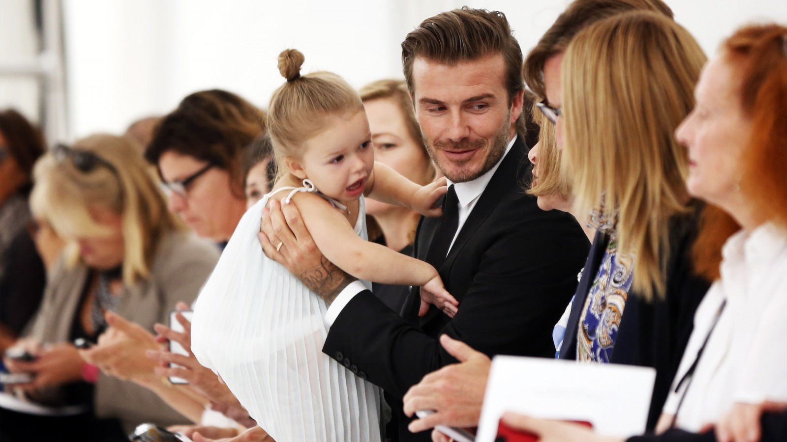 Former England soccer captain David Beckham holds his daughter Harper while waiting for a presentation of the Victoria Beckham Spring/Summer 2014 collection during New York Fashion Week, September 8, 2013. REUTERS/Lucas Jackson (UNITED STATES - Tags: FASHION ENTERTAINMENT SPORT SOCCER) - RTX13CVD