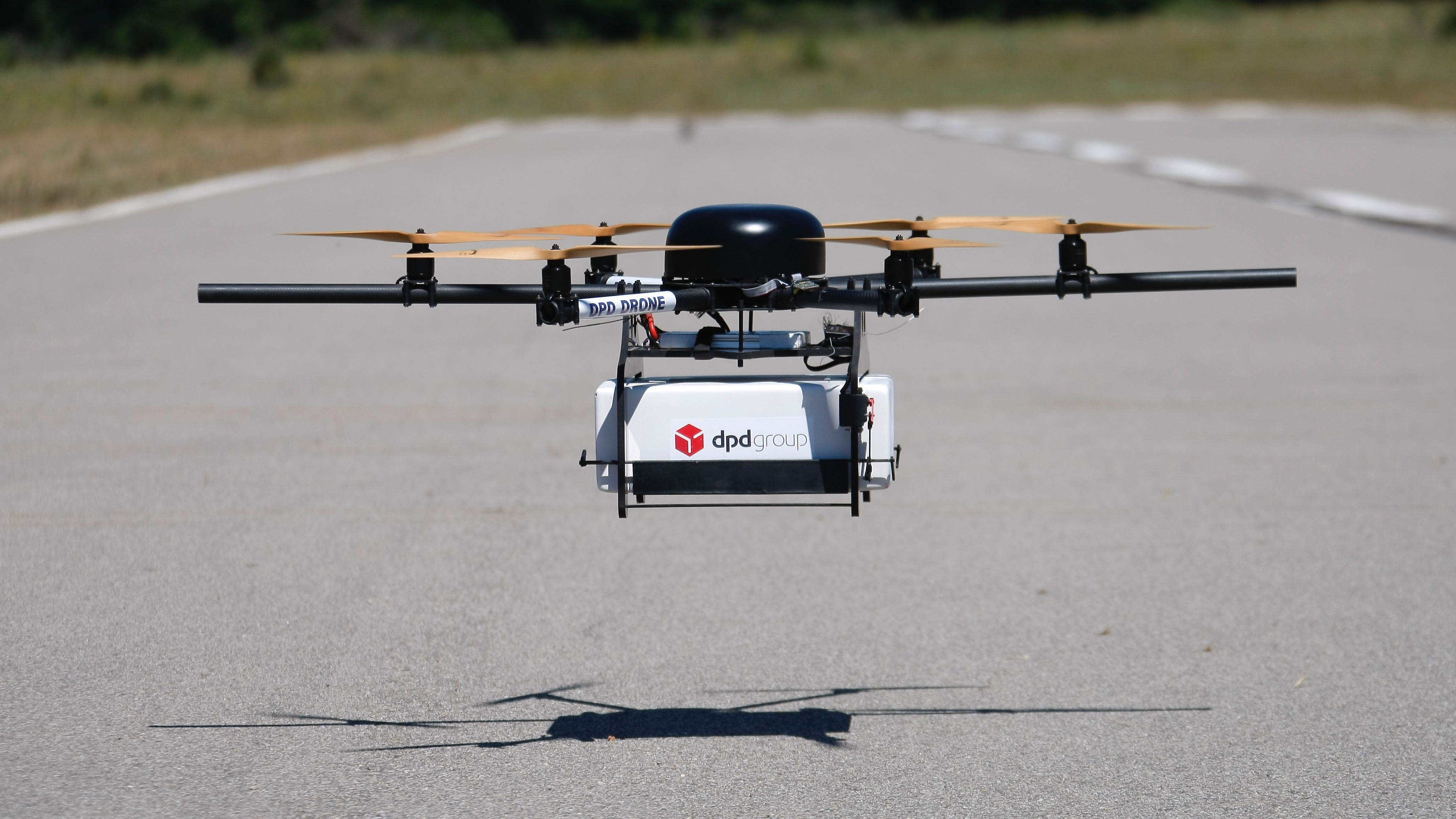 A DPD Geopost prototype drone files carrying a parcel flies during a test flight in Pourrieres, southern France, June 23, 2015. GeoPost, a package delivery subsidiary of LaPoste, is set to launch a programme which will see parcels delivered by drones. The GeoDrone completed its first successful automated flight last September. (AP Photo/Claude Paris)
