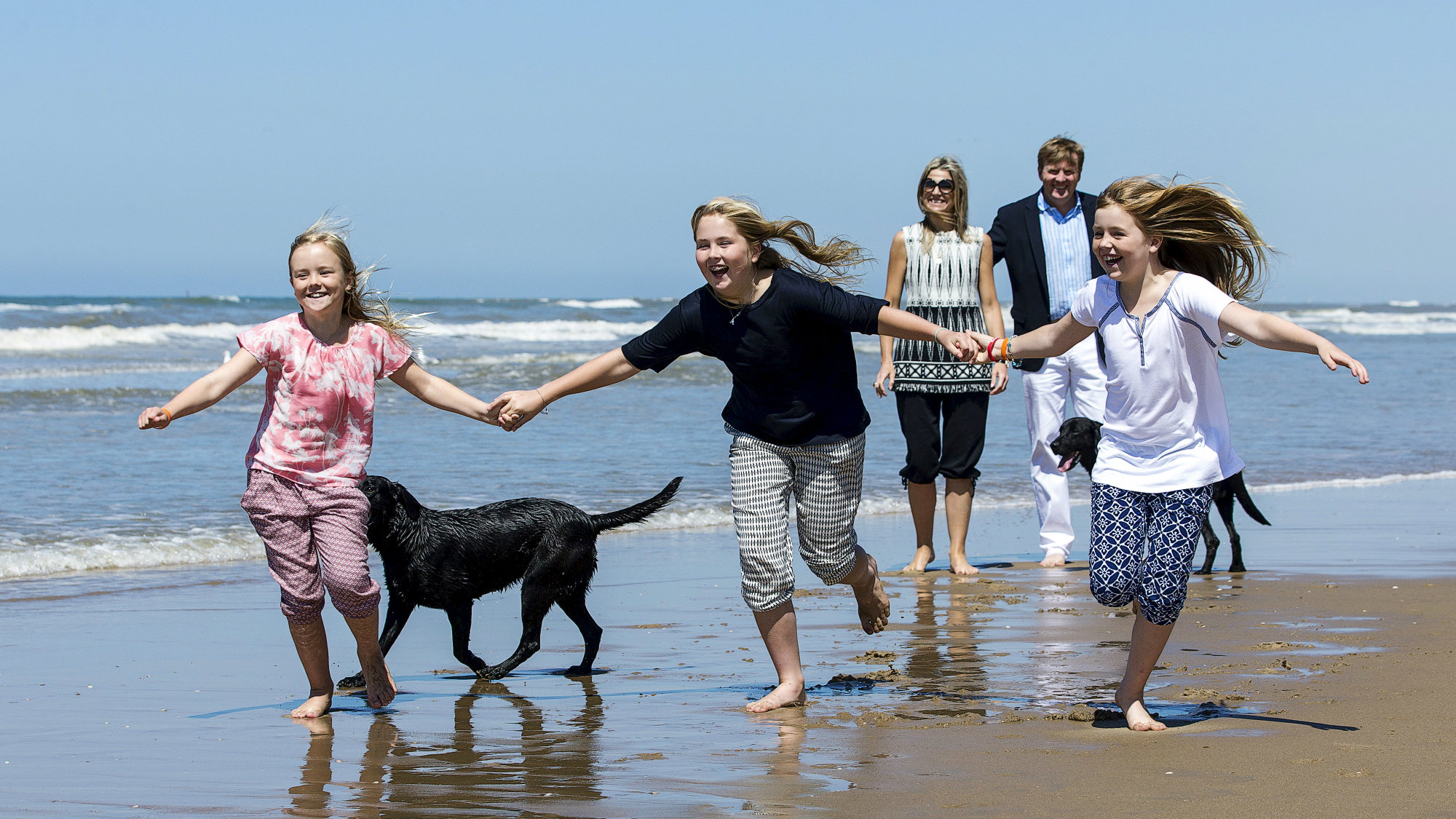 Princess Ariane (L), Princess Catharina-Amalia (C) and Princess Alexia (R), play on the beach during a photo session as their parents, King Willem-Alexander and Queen Maxima of the Netherlands look on near Wassenaar, the Netherlands, July 10, 2015.