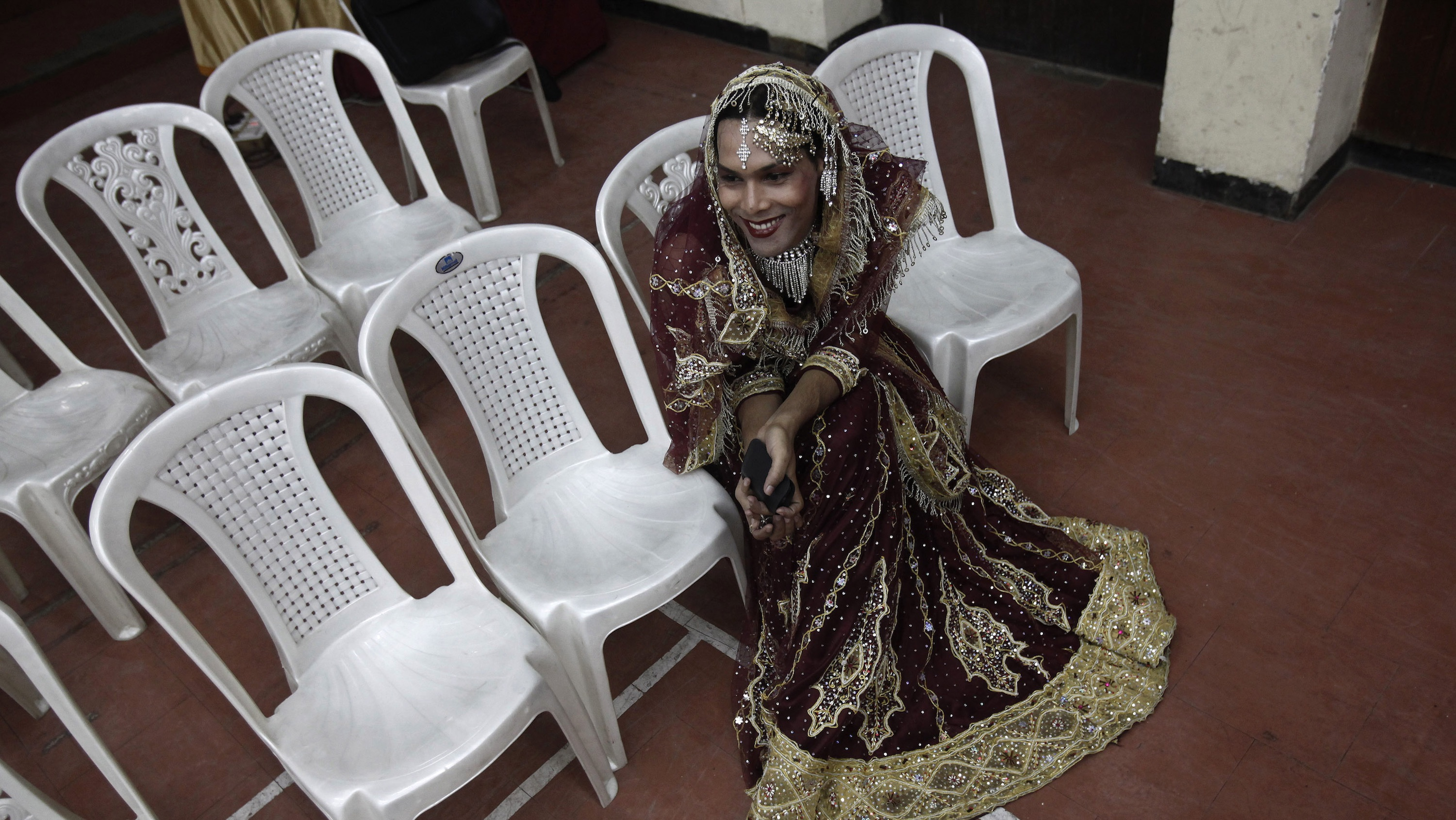 A hijra waits for her dance at a national hijra festival in New Delhi, India.