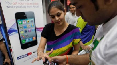 A salesperson, left, at a mobile phone shop helps a customer with the working of the Apple iPhone 4 in New Delhi, India, Friday, May 27, 2011. The Apple iPhone was launched in India Friday and is priced at 34,500 rupees ($747) for the 16GB and 40,900 rupees ($909) for the 32GB. (AP Photo/Manish Swarup)