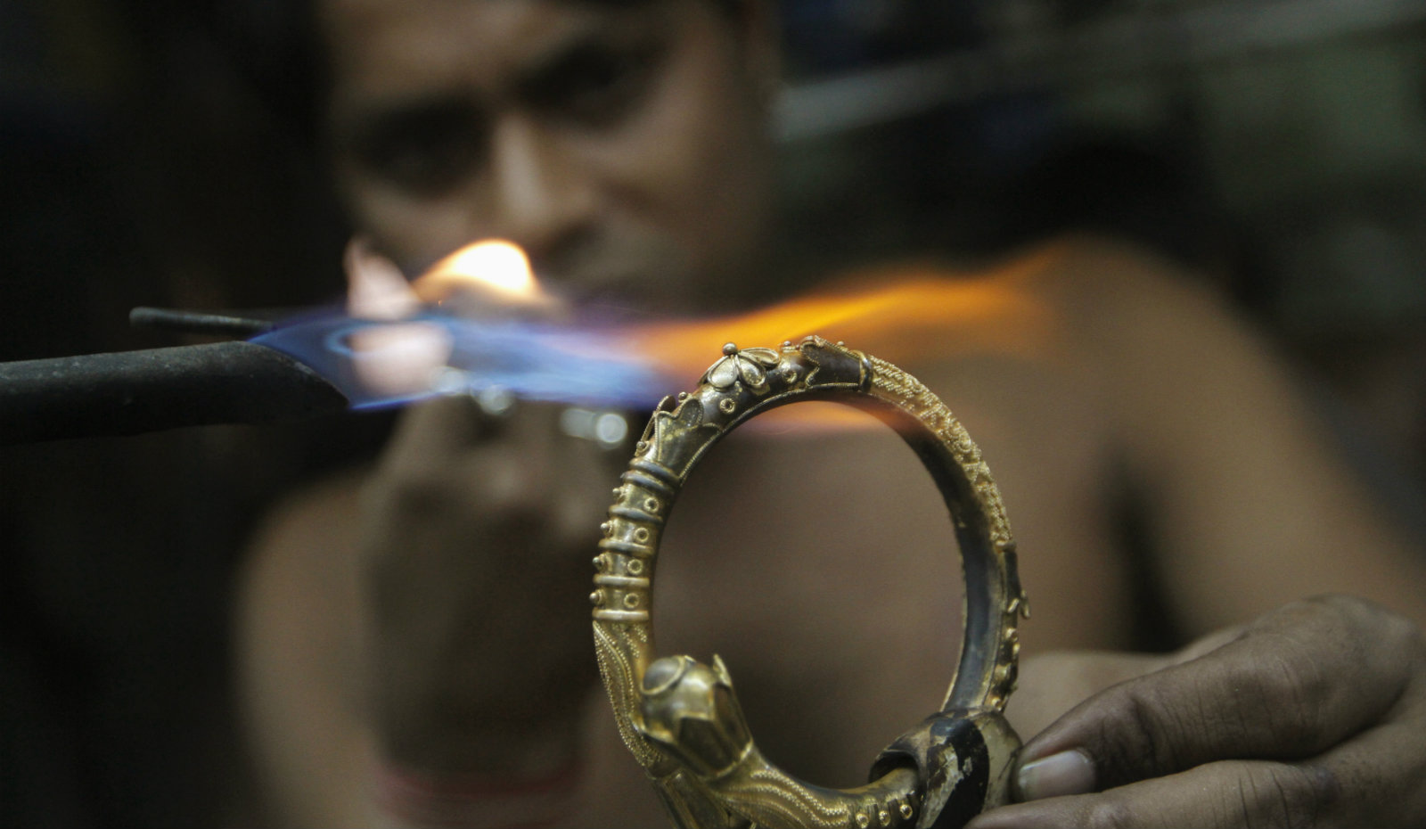 A goldsmith works on a gold bangle at a workshop in Kolkata January 16, 2013. India's passion for gold is putting such a strain on state finances that the government may slap higher import taxes on the precious metal, but demand buoyed by heady inflation and meagre savings will blunt the impact of any rise in duties.