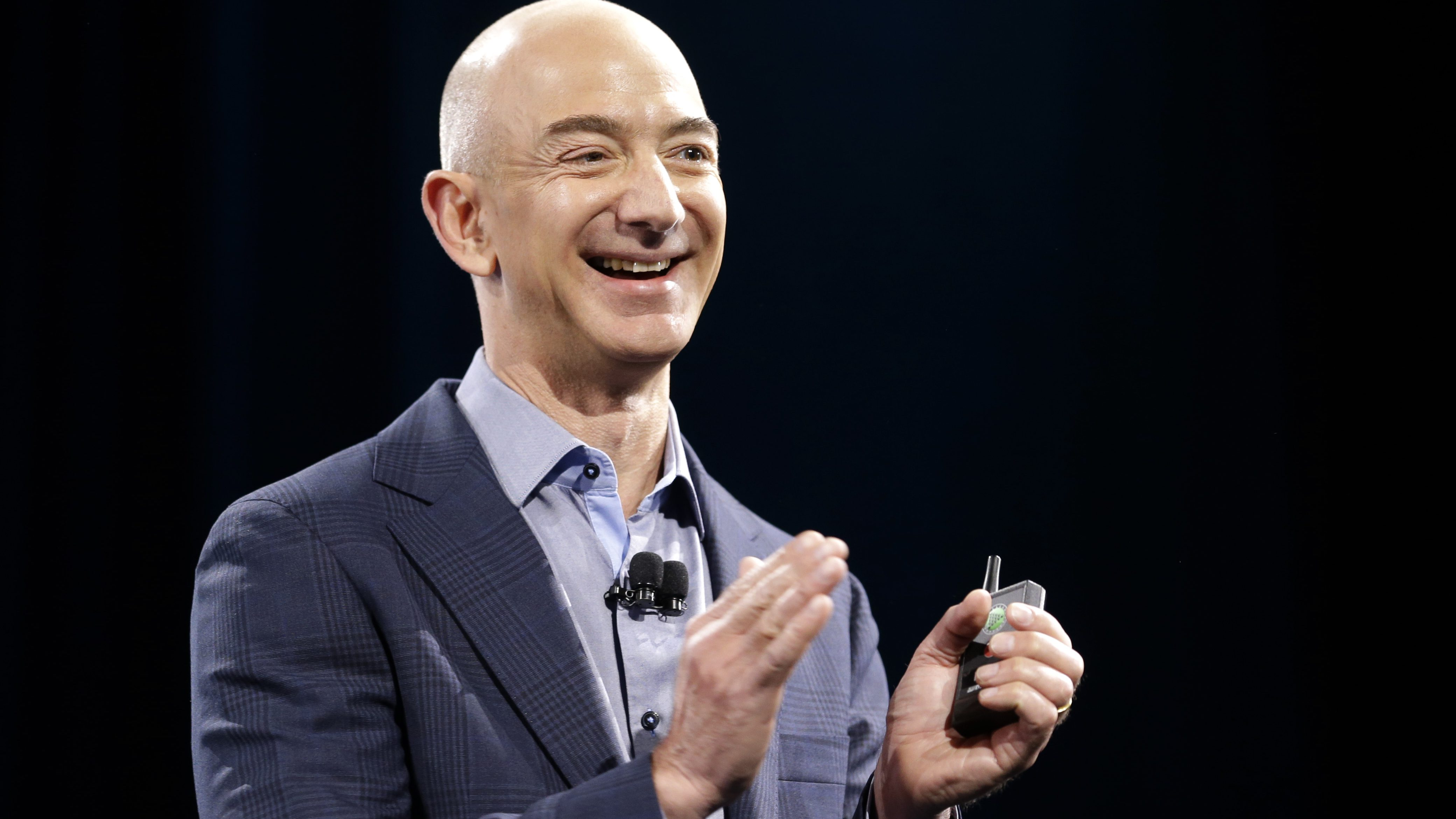 Amazon CEO Jeff Bezos holds a slide show controller and applauds at the start of the launch event for the new Amazon Fire Phone, Wednesday, June 18, 2014, in Seattle. (AP Photo/Ted S. Warren)
