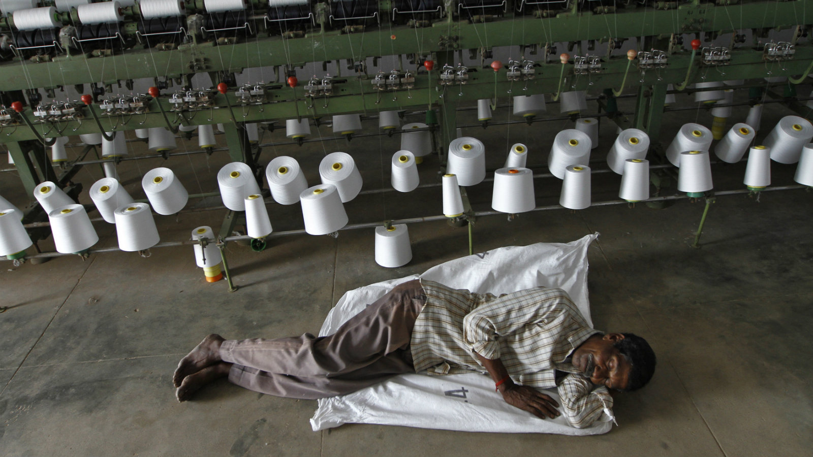 A worker takes a nap during a power cut in front of yarn-spinning equipment inside a factory in Coimbatore, about 500 km (310 miles) from the southern Indian city of Chennai, January 8, 2013. Crippling power cuts in the southern Indian state of Tamil Nadu are shutting factories and threatening an industrial debt crisis that is wrecking its second-largest city's plan to become the country's next business Mecca. Picture taken January 8, 2013.