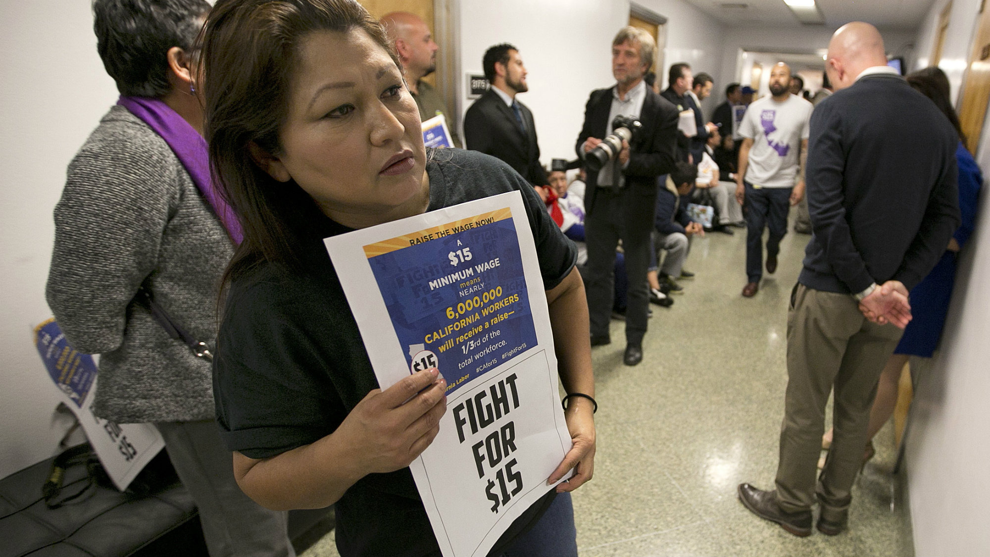 Teamster member Rocio Mejia, a supporter of a proposal to raise the state's minimum wage, joins others outside the Assembly Chambers calling for Assembly members to approve the measure, Thursday, March 31, 2016, in Sacramento, Calif.