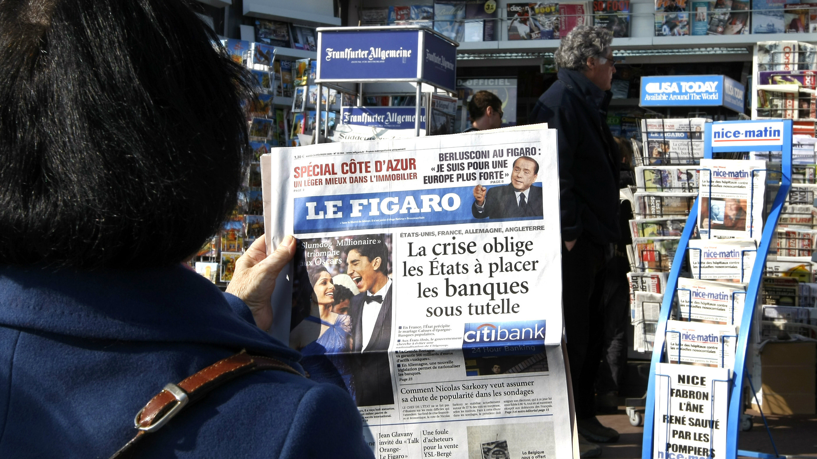 A woman reads the French daily newspaper Le Figaro next to a newsstand in Nice, southeastern France, February 24, 2009. The economic crisis has come at a difficult time for the media industry, but it may be helping those big players who put their magnetic brand power to use in winning online attention. According to data from OJD, the organisation that monitors media circulation in France, big newspapers like Le Figaro or Le Monde or other major titles like sports daily L'Equipe attract some of the biggest online readerships. Picture taken February 24, 2009. To match feature FRANCE-NEWS/INTERNET REUTERS/Eric Gaillard (FRANCE)