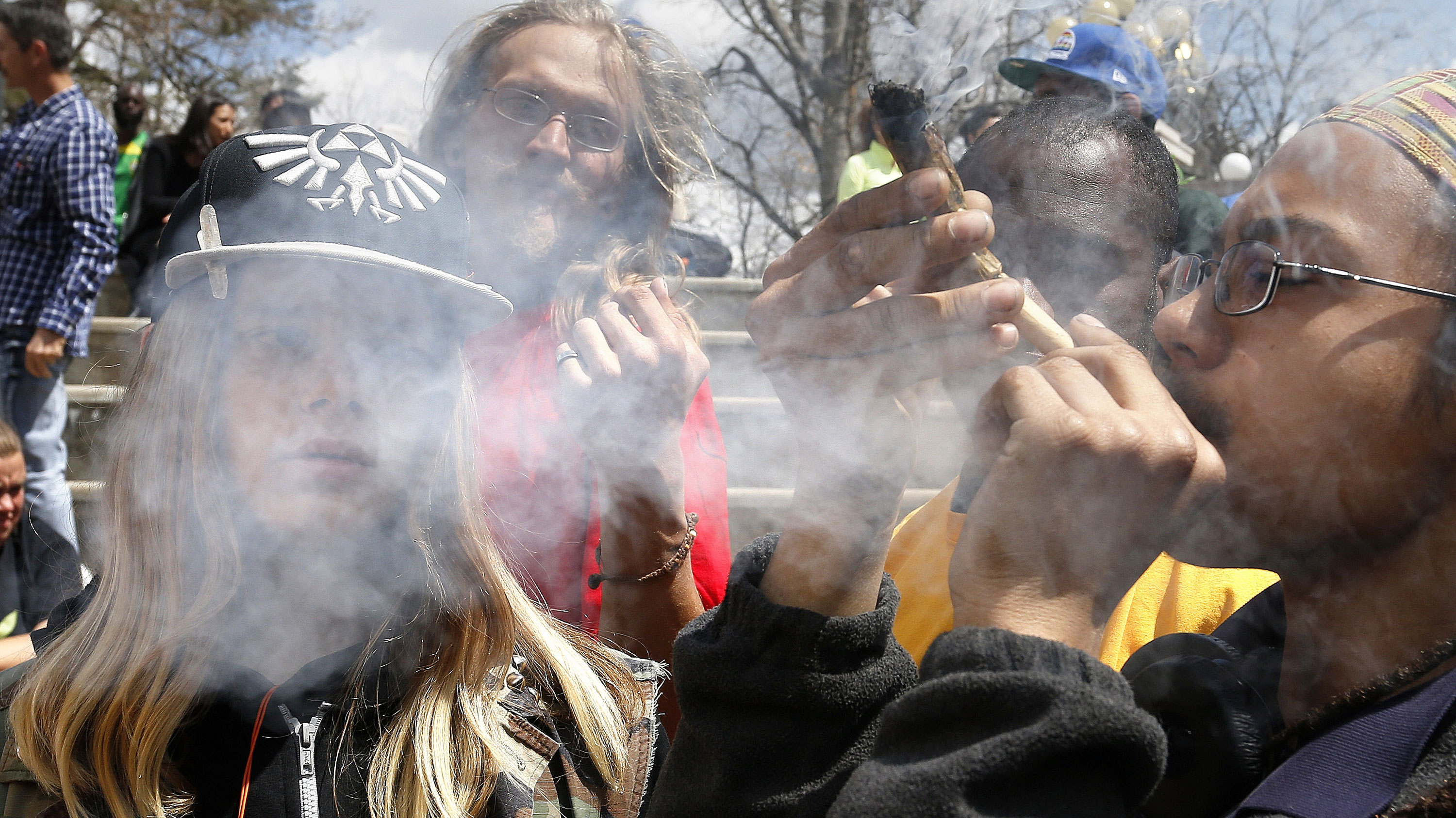 FILE - In this April 18, 2015 file photo, young partygoers listen to music and smoke marijuana during the annual 4/20 marijuana festival, in Denver's downtown Civic Center Park. Saying that weed tourists have nowhere to legally use the pot they're buying, marijuana activists in Denver have launched a ballot initative that would ask voters whether businesses open only to people 21 and older should be permitted to allow pot use. (AP Photo/Brennan Linsley, File)