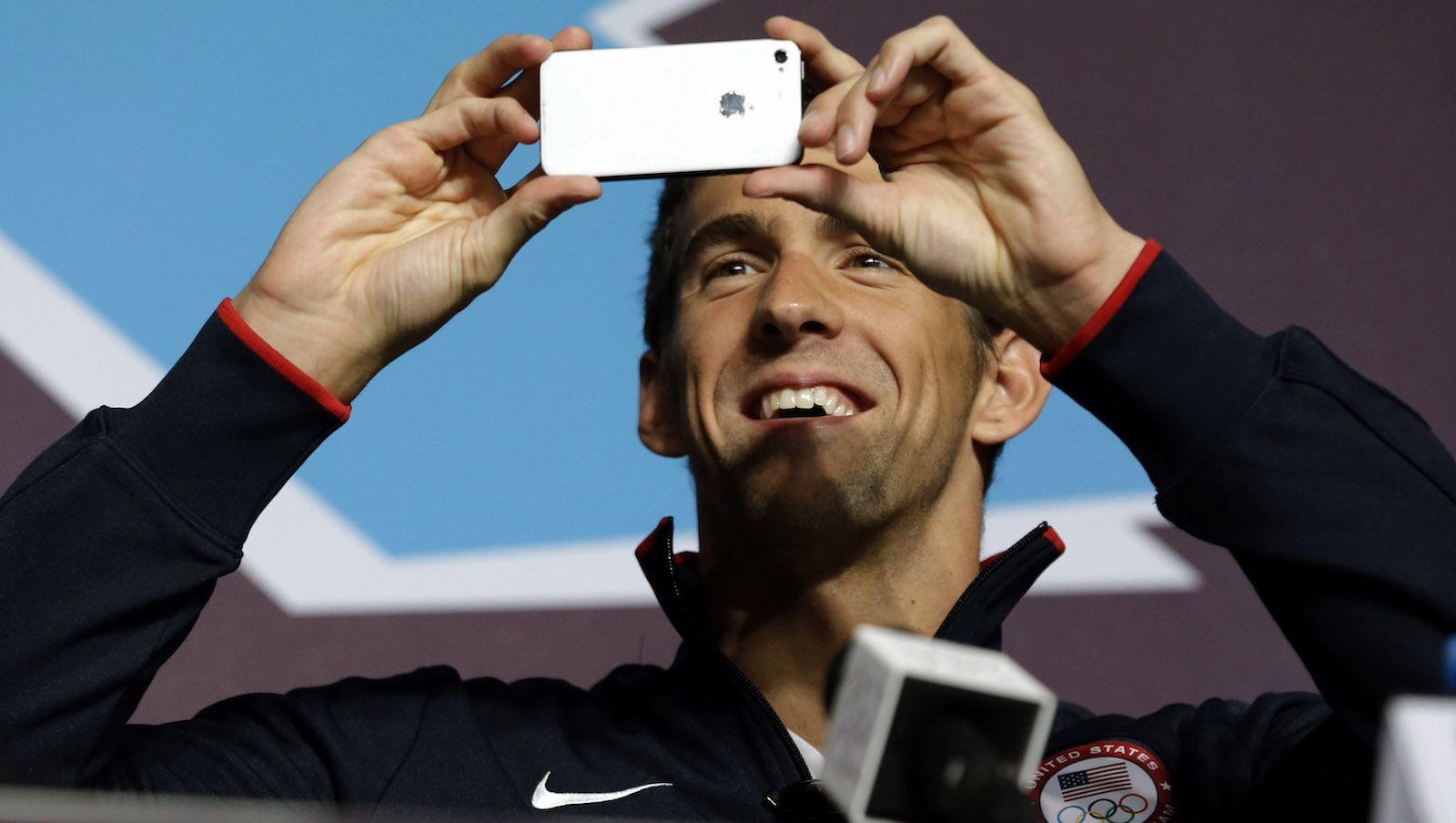 U.S. swimmer Michael Phelps uses his camera phone to take photos of journalists gathered at a press conference held at the media center of the 2012 Summer Olympics, Thursday, July 26, 2012, in London. Phelps insists these will be his last games. The 14-time gold medalist will go out with a bang, aiming to claim the unofficial title of greatest Olympian ever from Soviet gymnast Larisa Latynina. (AP Photo/Ng Han Guan)