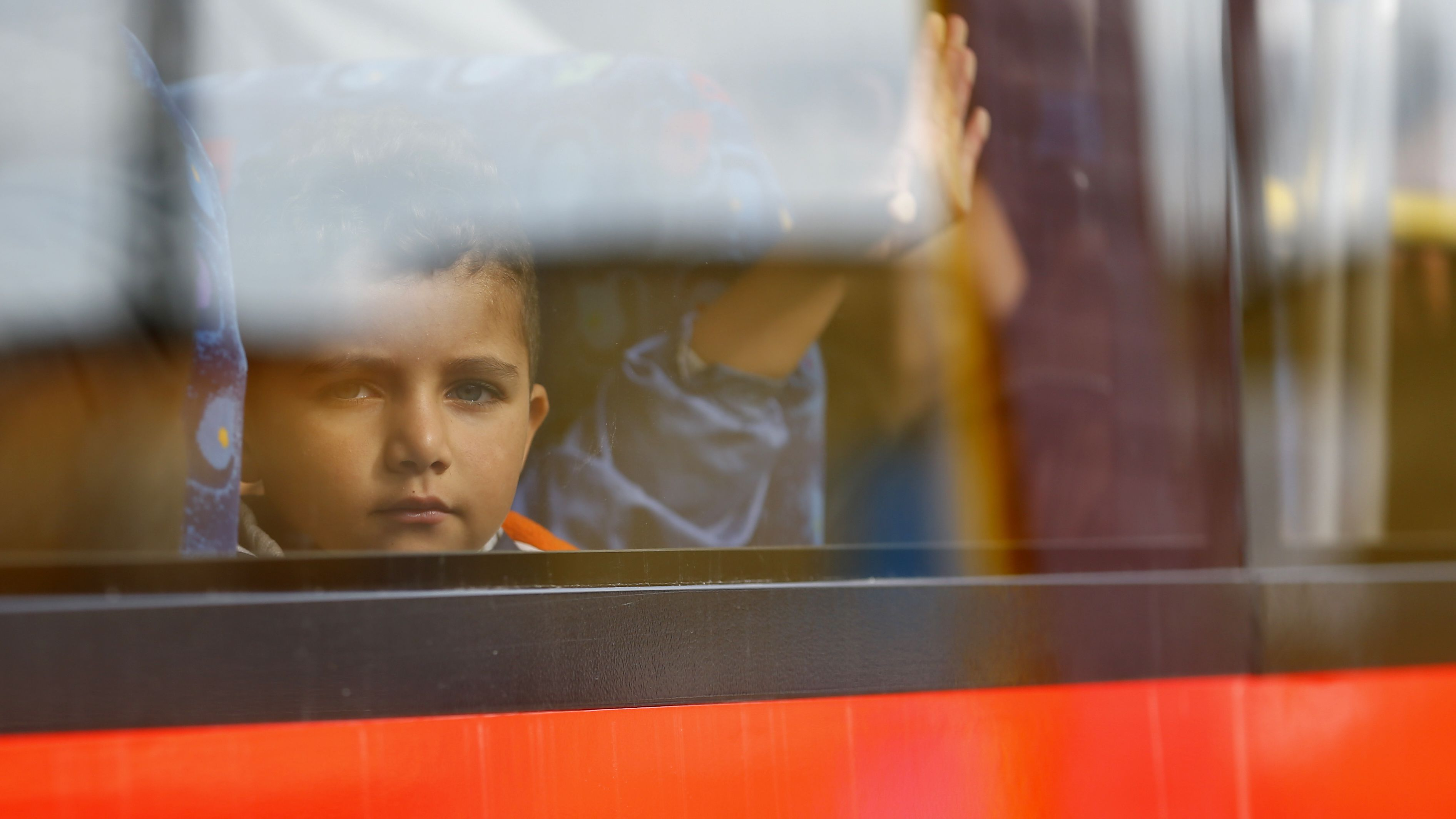 A migrant's child peers from a bus window near the border with Austria in Freilassing, Germany September 15, 2015. A total of 4,537 asylum seekers reached Germany by train on Monday despite the imposition of new controls at the border with Austria, the federal police said on Tuesday. The arrivals brought the number of asylum seekers who have entered Germany by train since the start of the month to 91,823, a police spokeswoman in Potsdam said. REUTERS/Dominic Ebenbichler