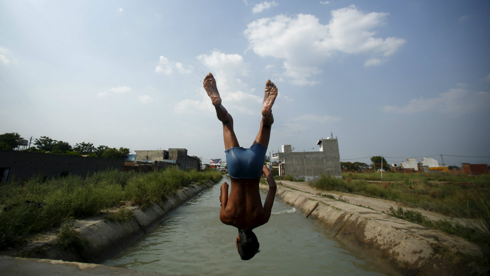 A boy jumps into a water canal on a hot summer day in Uttar Pradesh, India, June 4, 2015. India's finance minister on Thursday dismissed fears of the first drought in six years, just days after the weather office downgraded the forecast for monsoon rains this summer.
