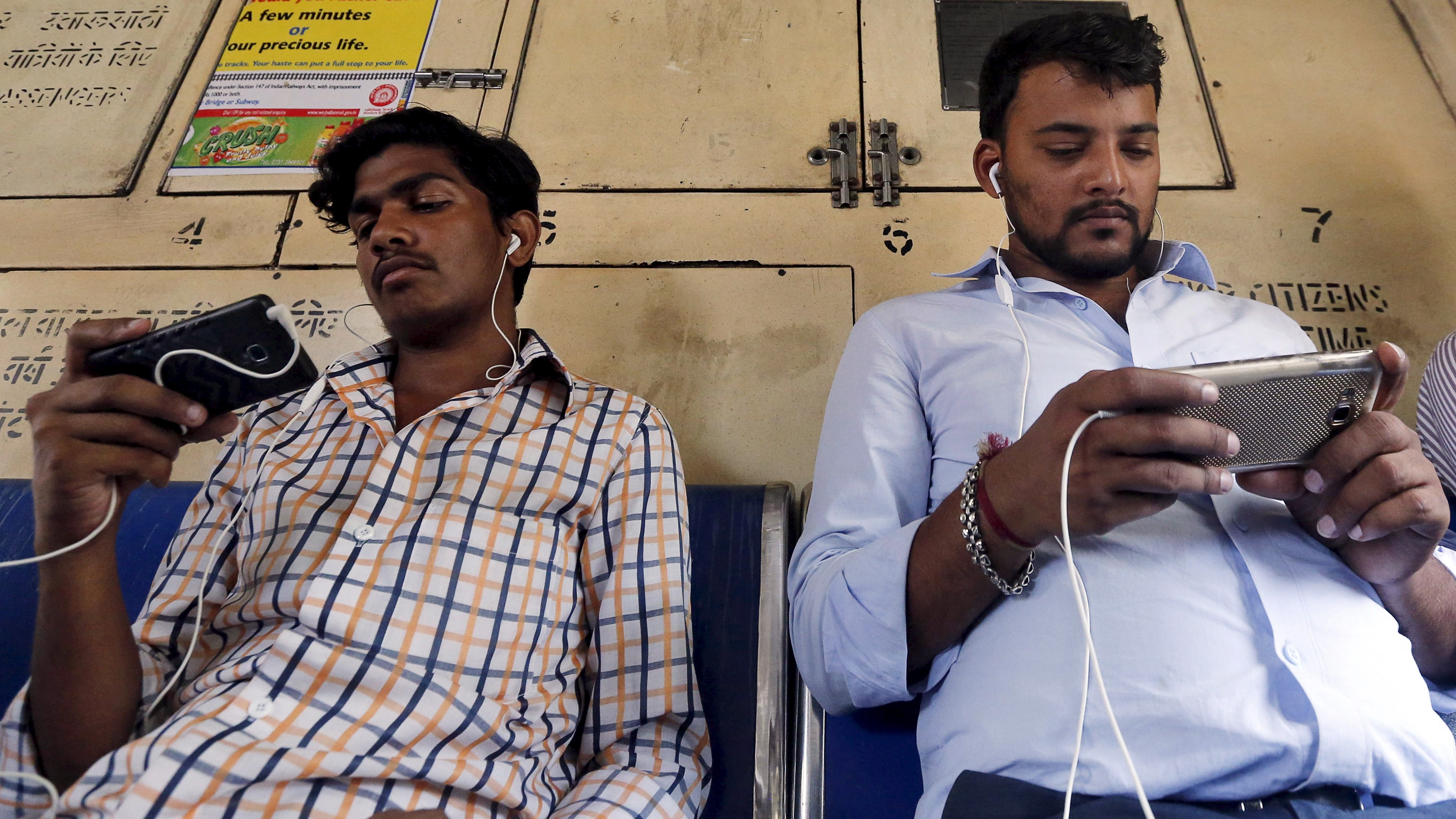 Commuters watch videos on their mobile phones as they travel in a suburban train in Mumbai