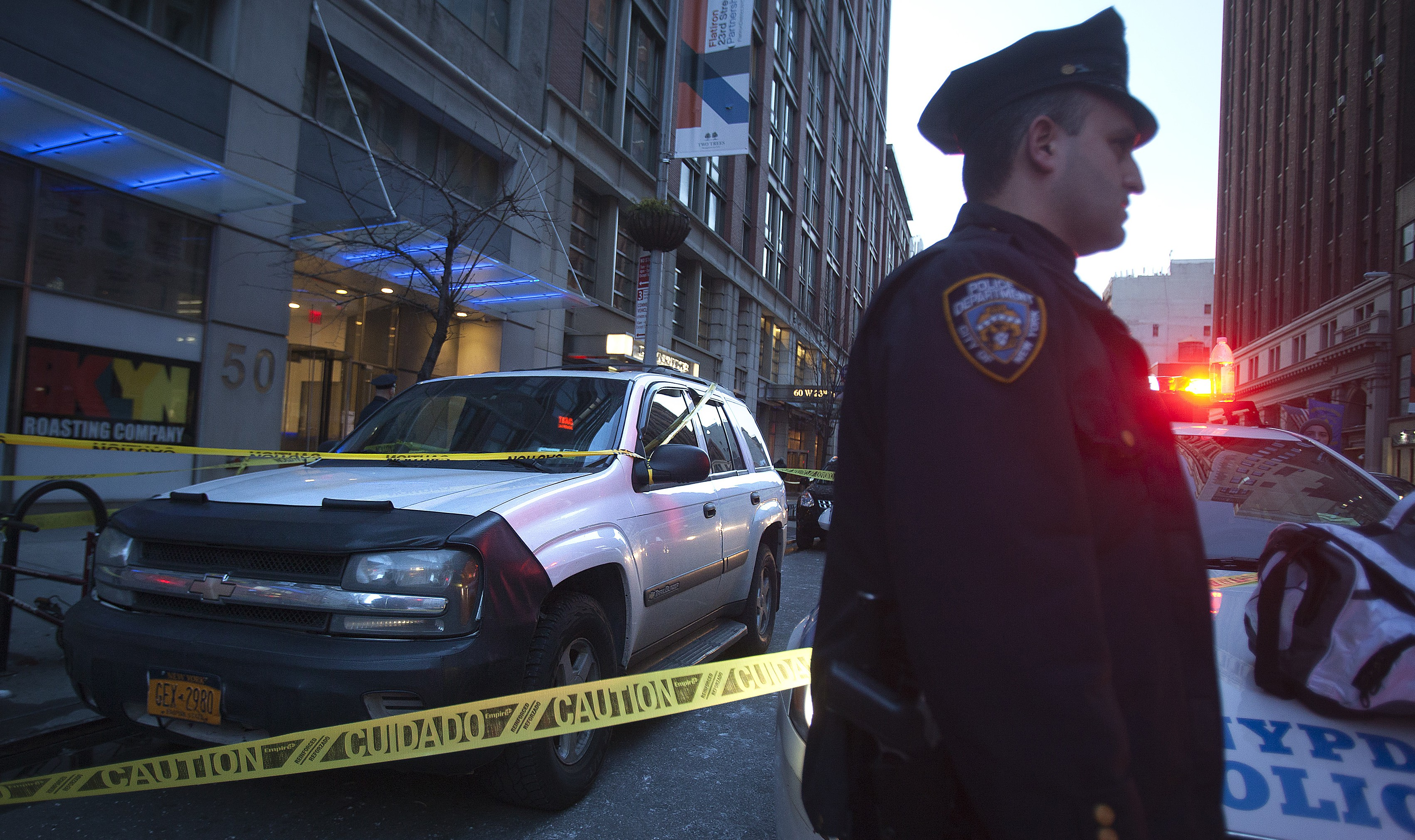 Police stand guard near a car, believed to belong to the suspect, outside a Home Depot store following a shooting in Manhattan's Chelsea neighborhood of New York, January 25, 2015. Two people were killed after a shooting in the store on Sunday afternoon in what appears to be a murder-suicide, two New York Police Department (NYPD) spokesmen said.