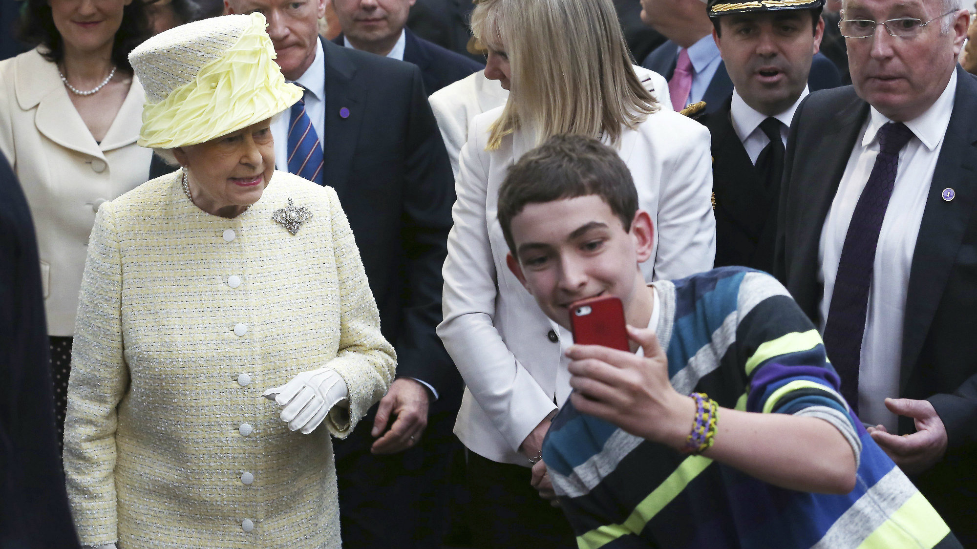 A local youth takes a selfie in front of Britain's Queen Elizabeth in St George's indoor market in Belfast, Northern Ireland June 24, 2014.