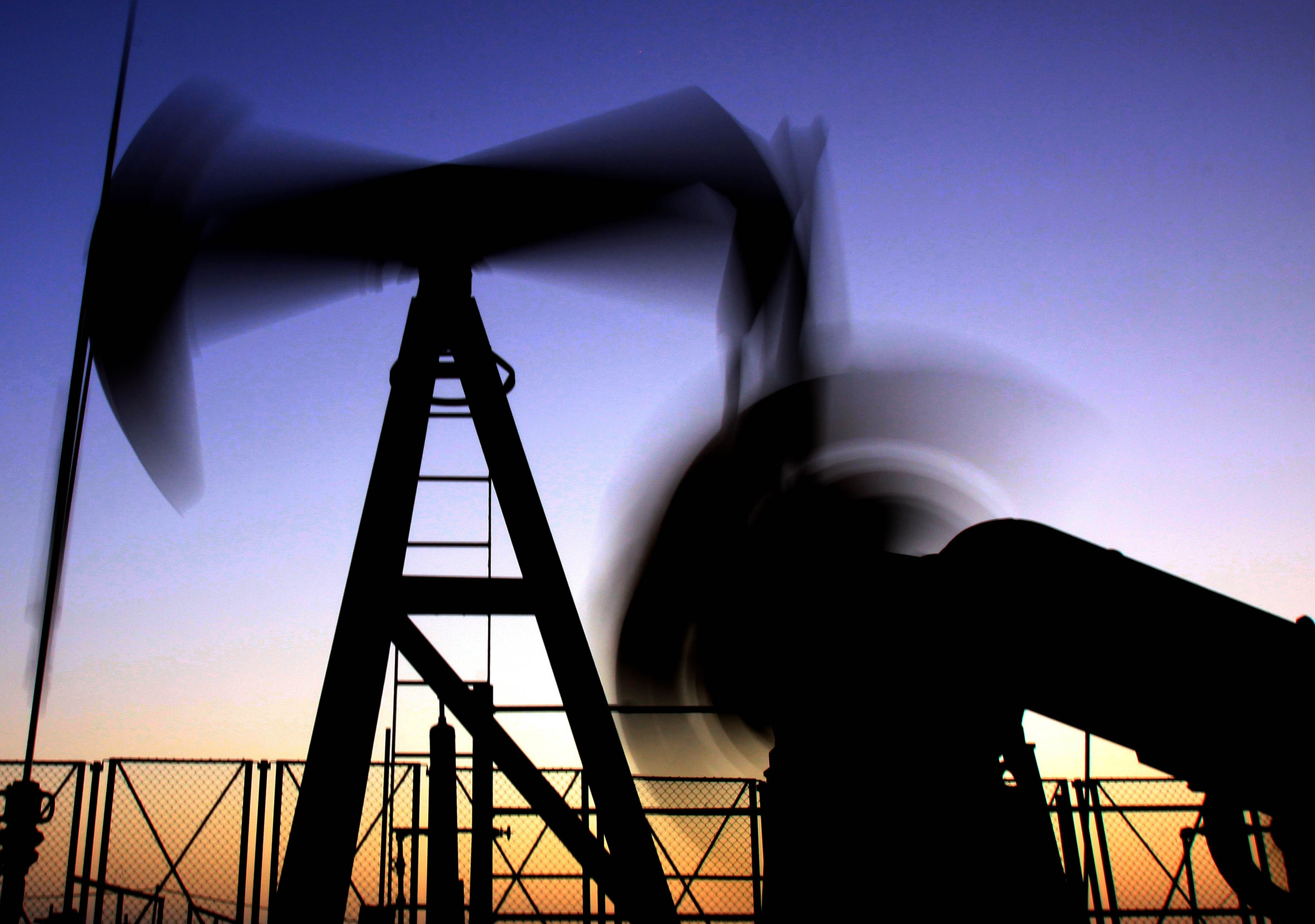 In this May 29, 2009 file photo, an oil rig works in the desert oil field of Sakhir, Bahrain. Crude oil followed the stock market up on Tuesday, Jan. 19, 2010, settling higher for the first time in five sessions.