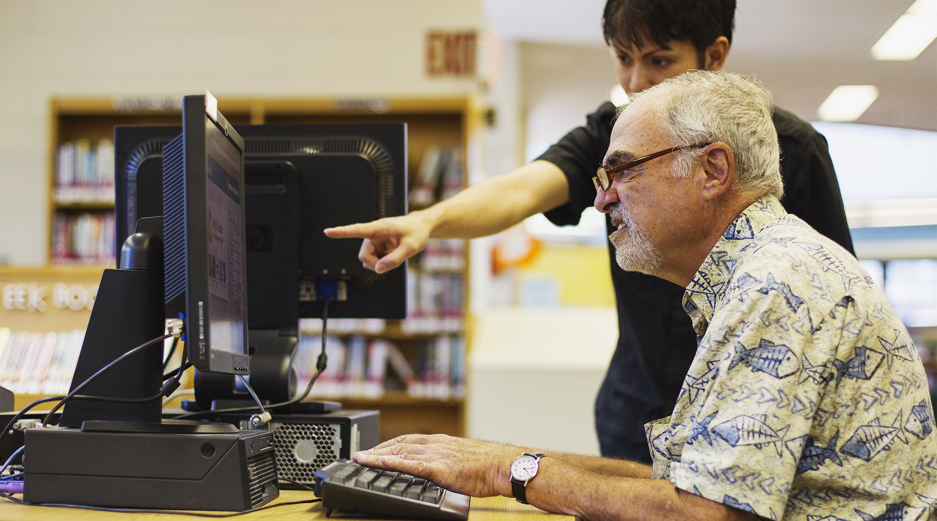 A librarian teaches a senior citizen how to use a Facebook account during a class at a branch of the New York Public Library in New York