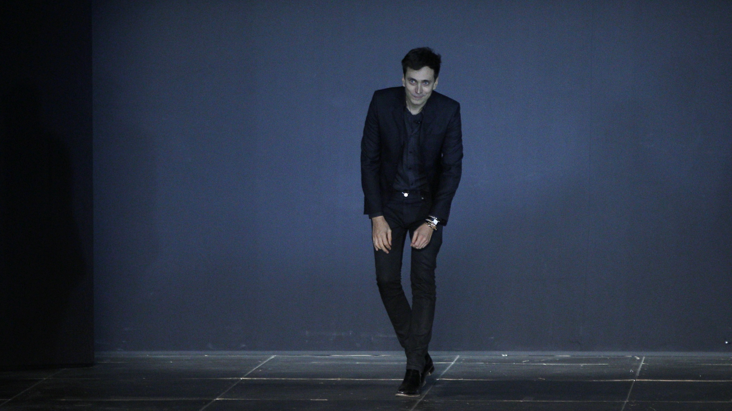 French designer Hedi Slimane appears at the end of his Spring/Summer 2013 women's ready-to-wear fashion show for French fashion house Saint Laurent Paris during Paris fashion week October 1, 2012.