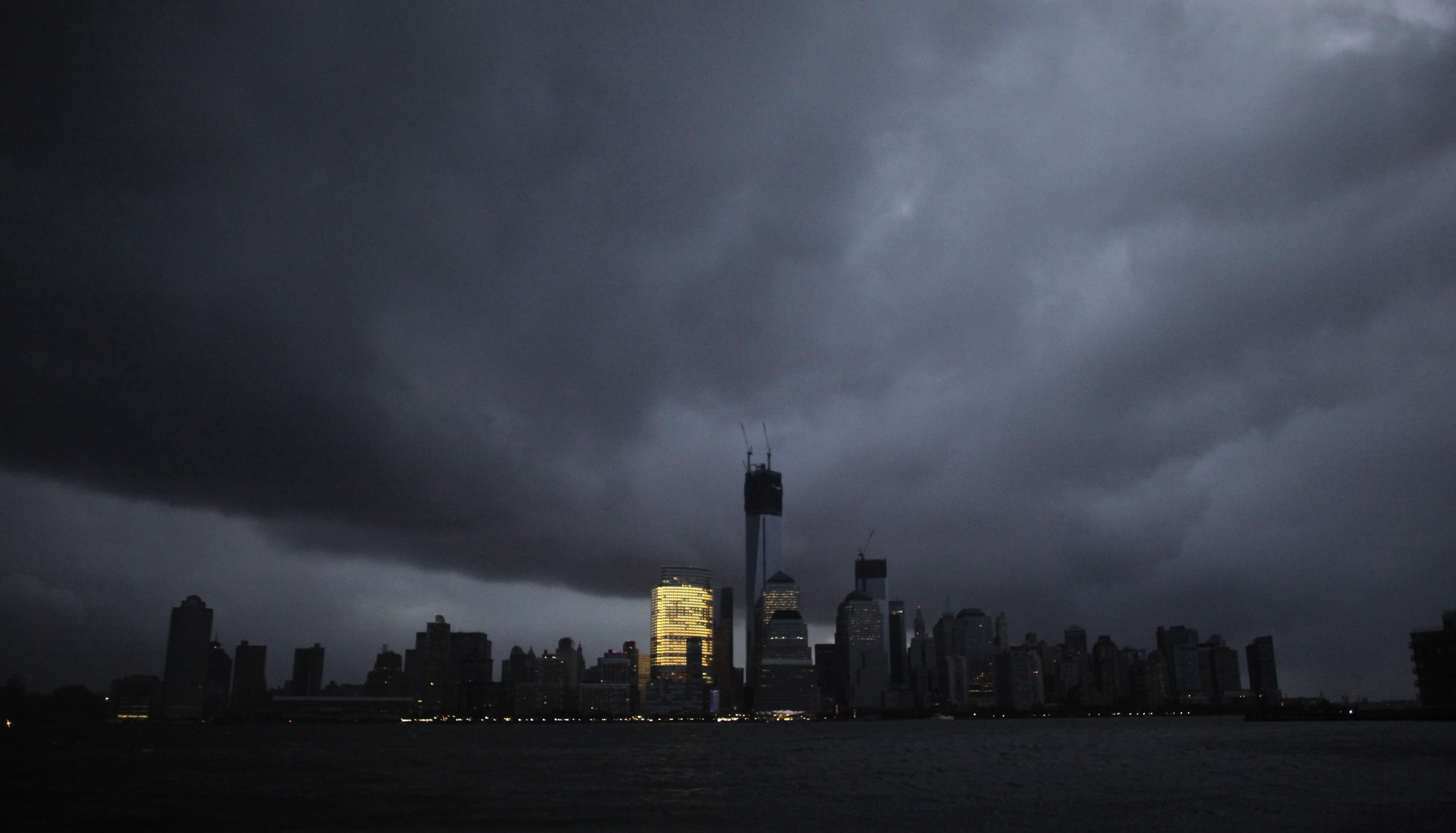 The skyline of lower Manhattan is in darkness except for Goldman Sachs building after a preventive power outage caused by giant storm Sandy as seen from Exchange Place,  in New York