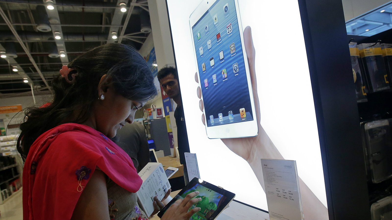 A customer tries out an Apple iPad Mini in the Apple specialty section of a Croma retail store in Mumbai February 22, 2013. The store offers Apple products including iPhones and iPads on instalment plans. More than four years after it started selling iPhones in India, Apple Inc is now aggressively pushing the iconic device through instalment payment plans that make it more affordable, a new distribution model and heavy marketing blitz. The result: iPhone shipments to India between October and December of 2012 nearly tripled to 250,000 units from 90,000 in the previous quarter, according to an estimate by Jessica Kwee, a Singapore-based analyst at consultancy Canalys. Picture taken February 22, 2013.
