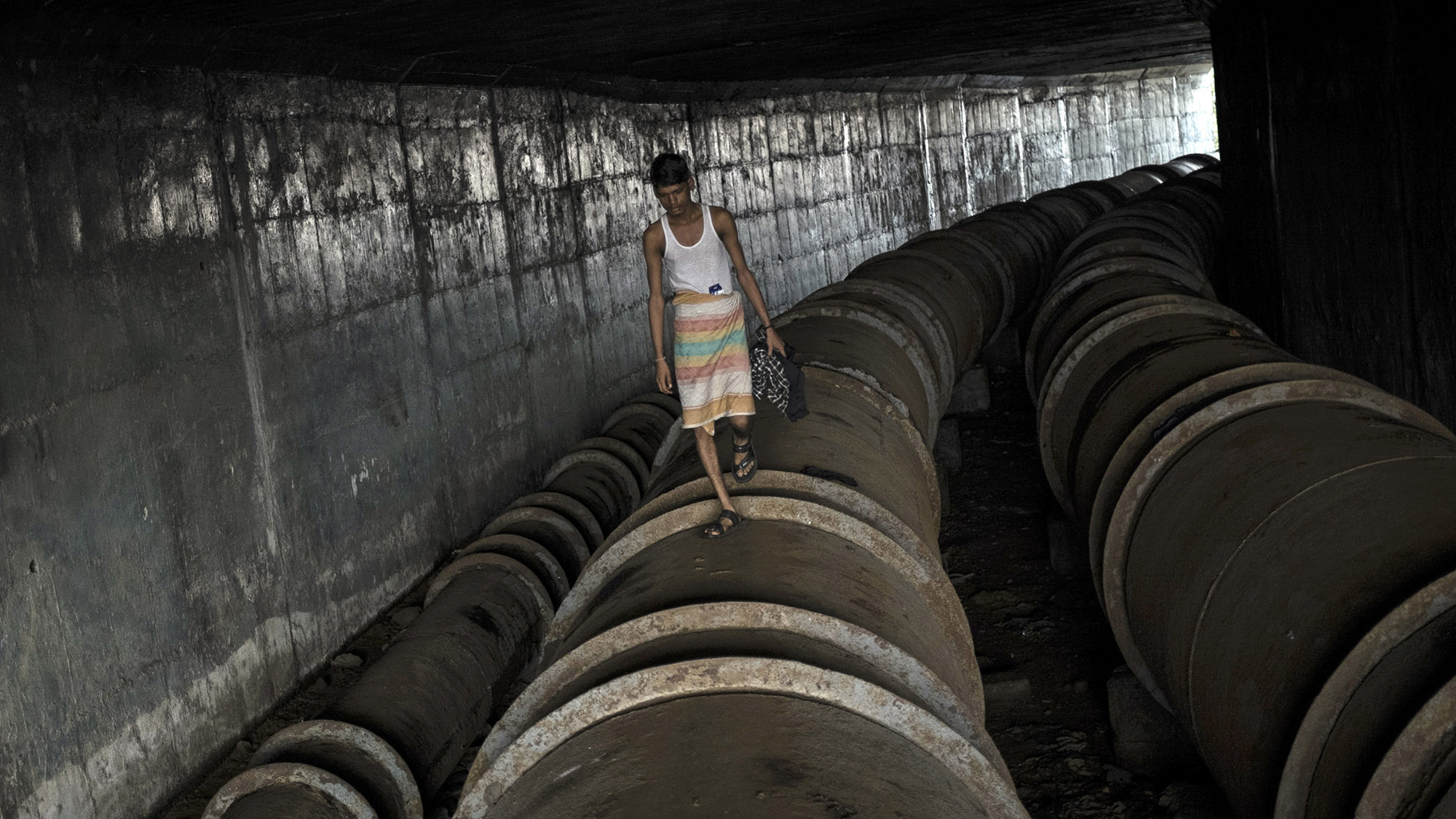 A man walks on a water pipeline used a as pathway under a bridge in Mumbai August 8, 2014. REUTERS/Danish Siddiqui (INDIA - Tags: SOCIETY) - RTR41NNP