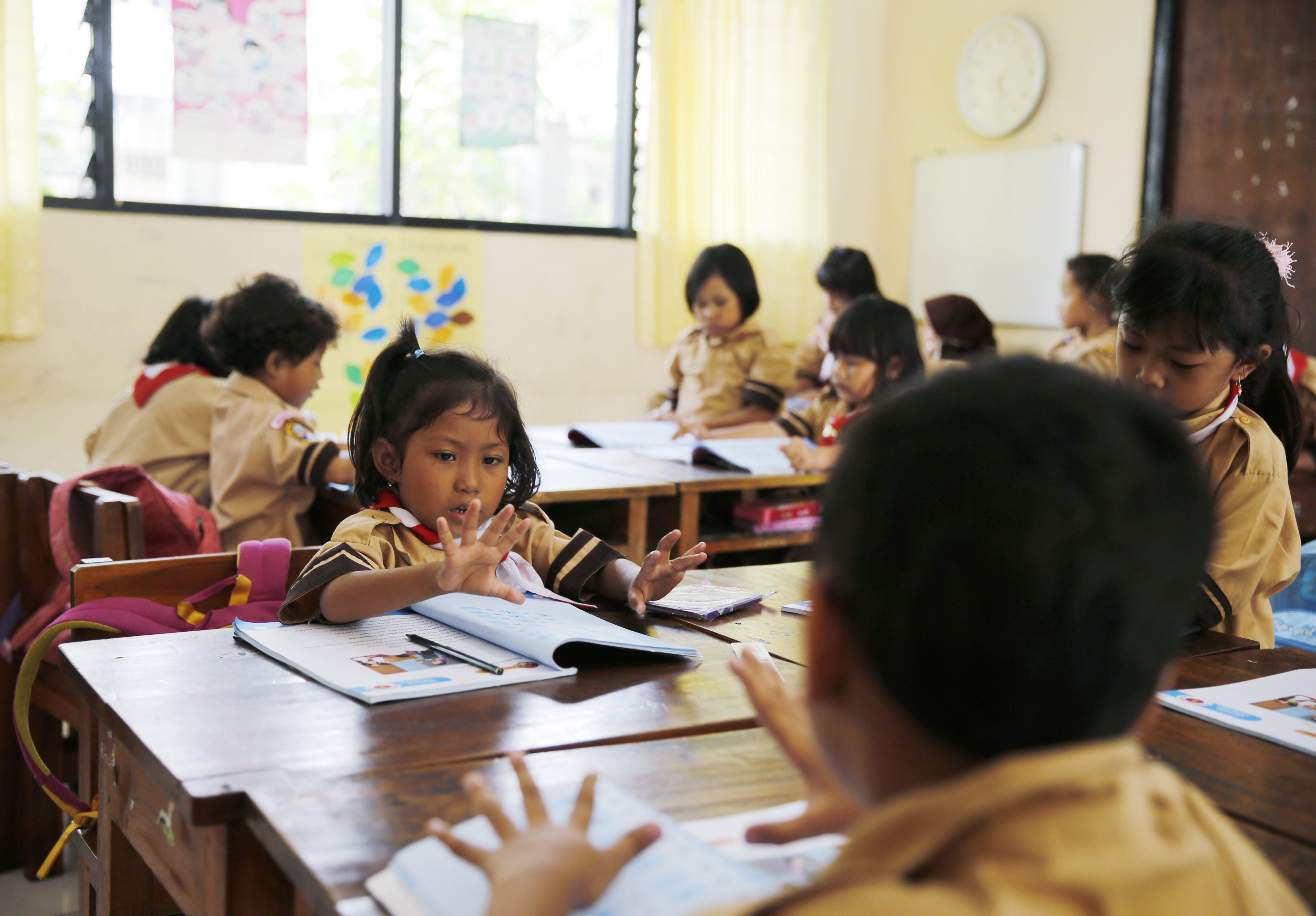 Students count with their fingers as a teacher teaches the 2013 curriculum inside a classroom at Cempaka Putih district in Jakarta