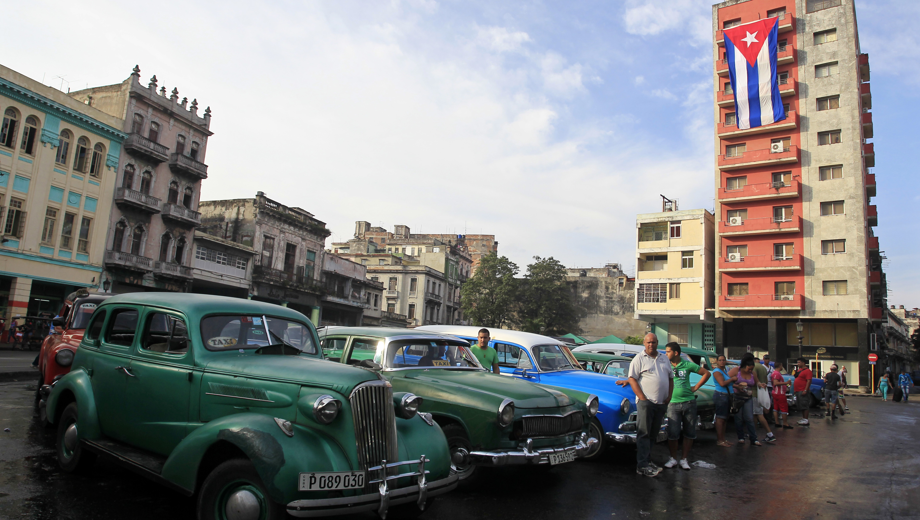 Vintage cars used as taxis are parked on a street in Havana