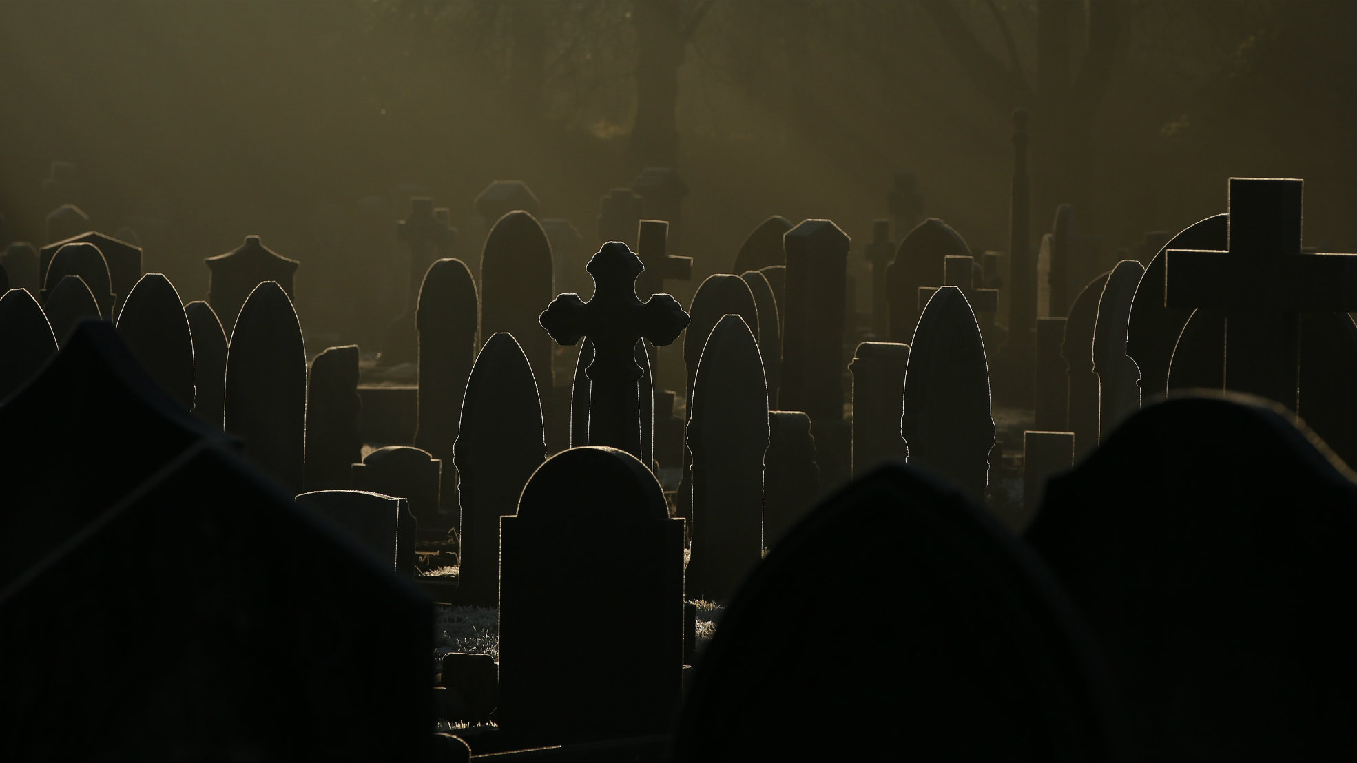 Sunlight glints off frost-covered gravestones in a cemetery in Altrincham, northern England.