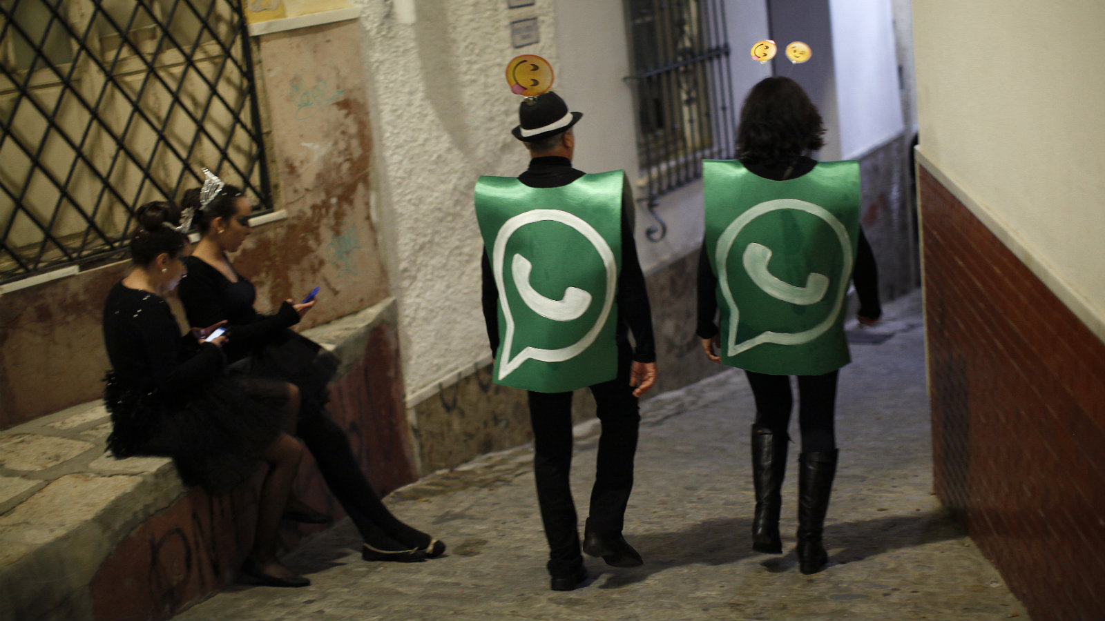 Revellers dressed up as dancers of 'Black Swan' check their mobile phones next to revellers dressed up as a Whatsapp logo as they take part in New Year's celebrations in Coin, near Malaga, southern Spain, early January 1, 2015. Villagers and revellers dressed up in funny costumes to take part in the New Year's celebration.