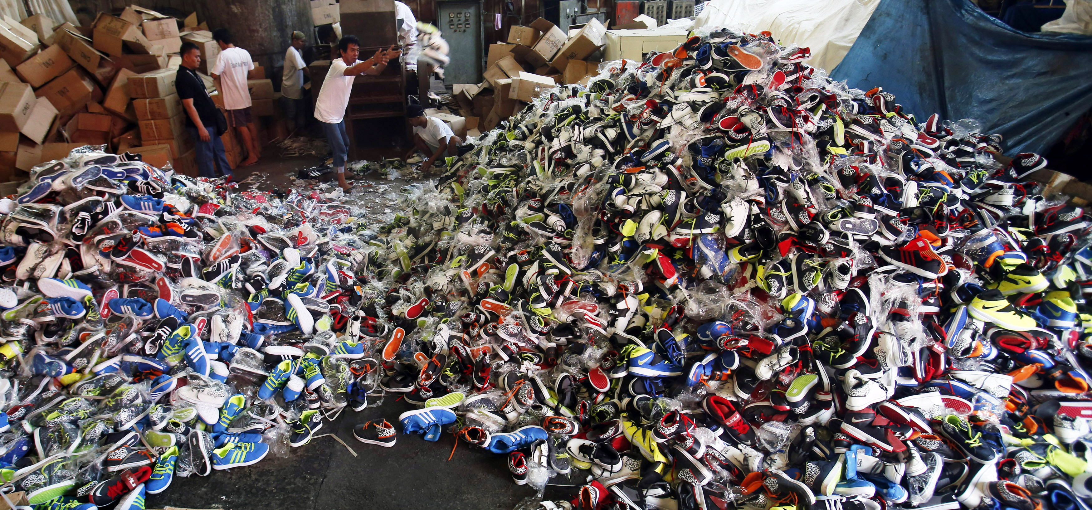 Government workers from the Bureau of Customs destroy counterfeit footwear products in Manila February 24, 2015. A government statement said over 150,000 pairs of fake shoes and slippers of various brands including Nike, Adidas, Converse, Sketchers, North Face, Leaveland, Merrell, Lacoste, Vans, Havaianas and Ipanema worth PHP 50 million ($1.13 million), which were smuggled from China, were destroyed at a government warehouse in Manila on Tuesday.