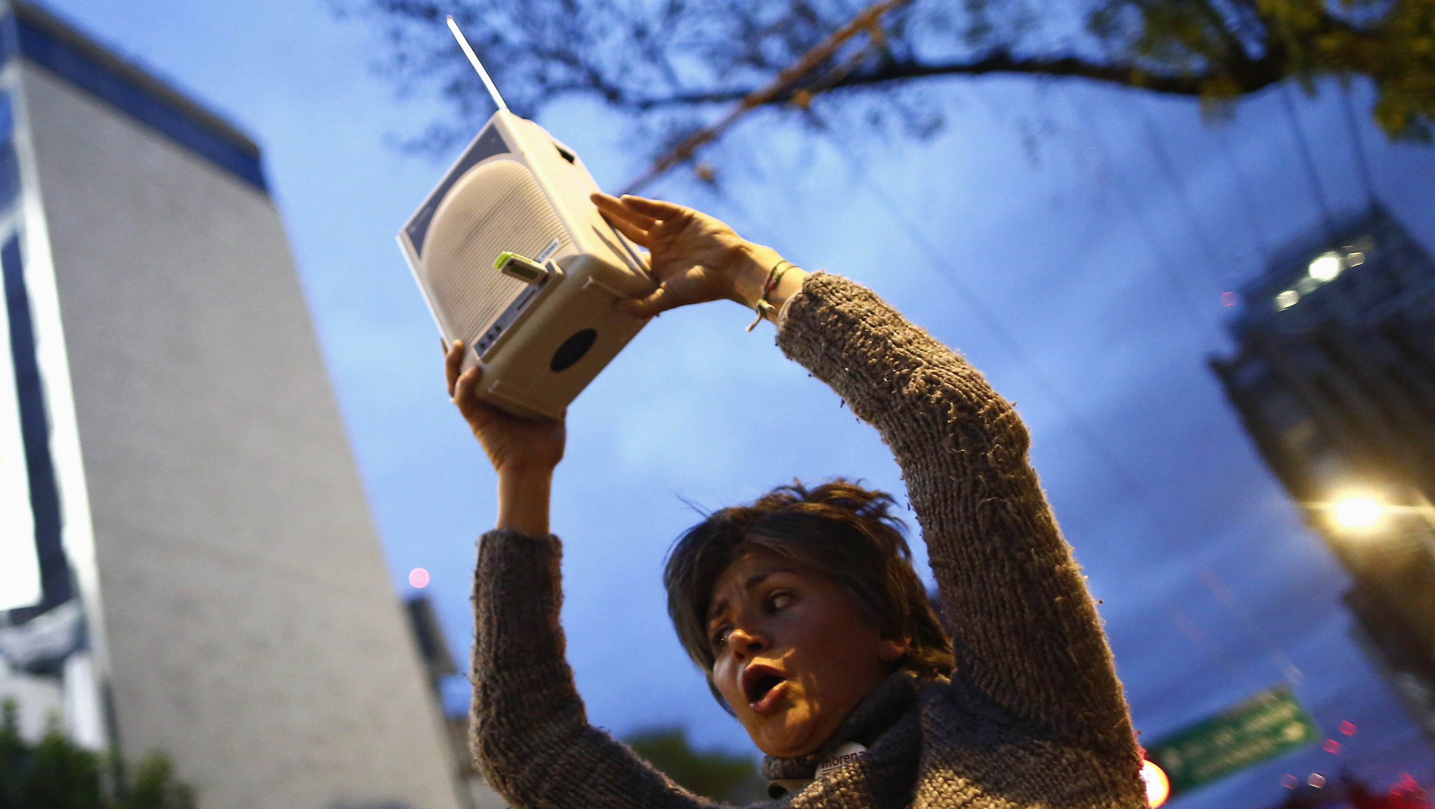 A supporter holds a radio during a protest against the dismissal of Mexican journalist Carmen Aristegui, outside MVS Radio's station building in Mexico City