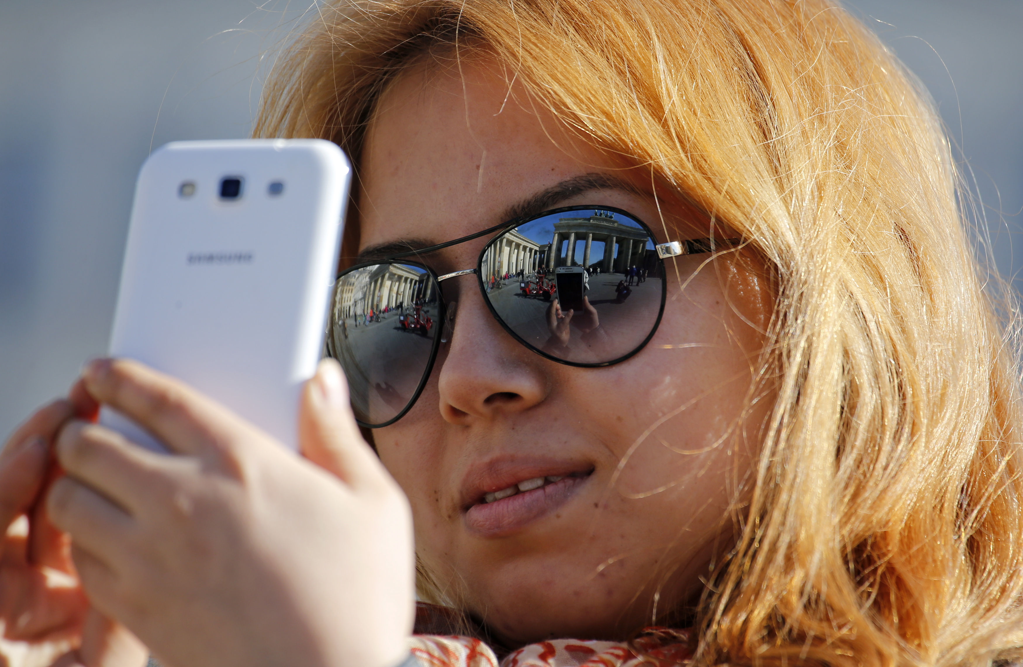 A tourist takes pictures with her mobile phone as Berlin's landmark Brandenburg Gate is reflected in her sunglasses during a sunny spring day in Berlin March 18, 2015.  (GERMANY  - Tags: CITYSCAPE SOCIETY)   - RTR4TUIN