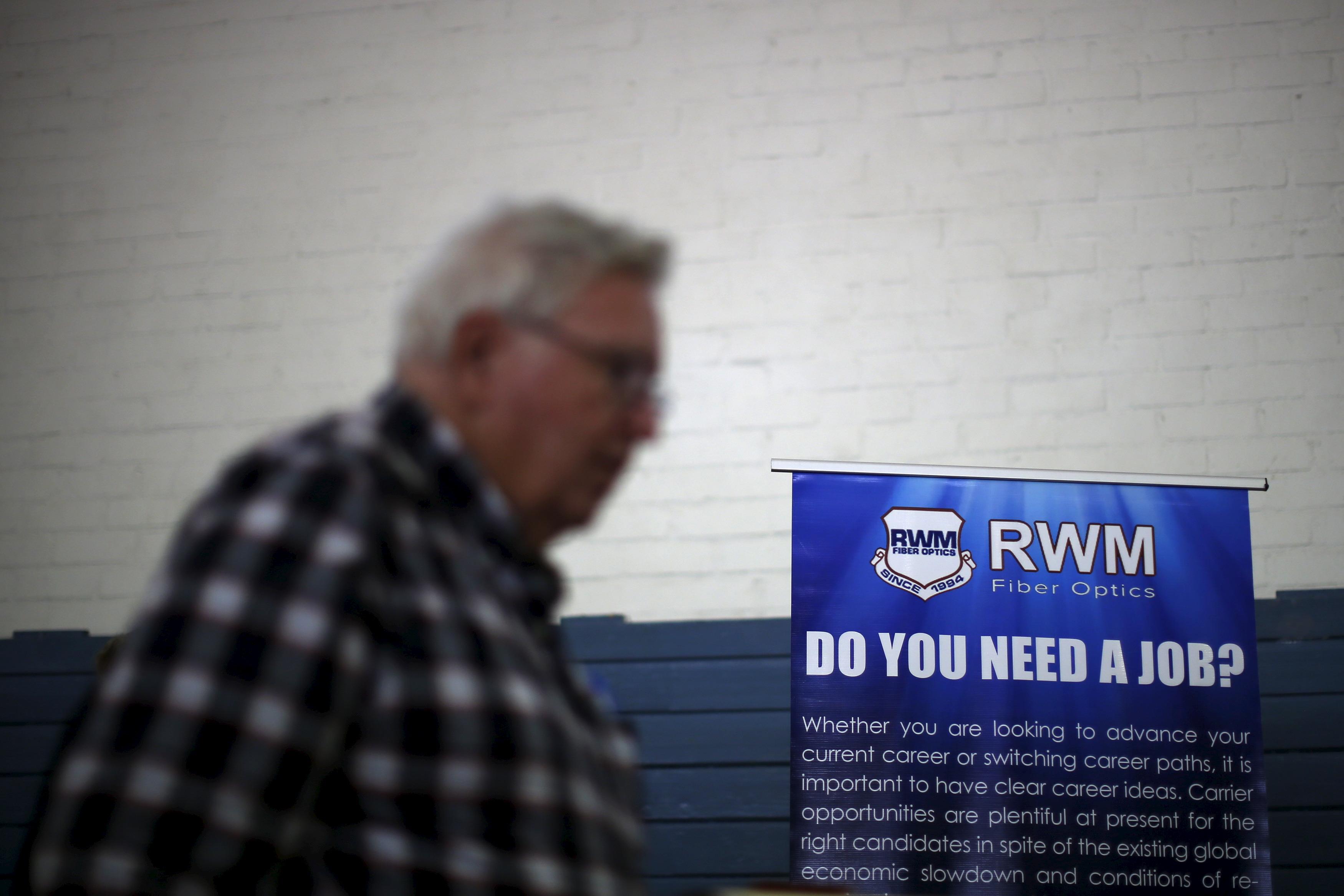 A job seeker walks past a sign at a veterans' job fair in Burbank, Los Angeles