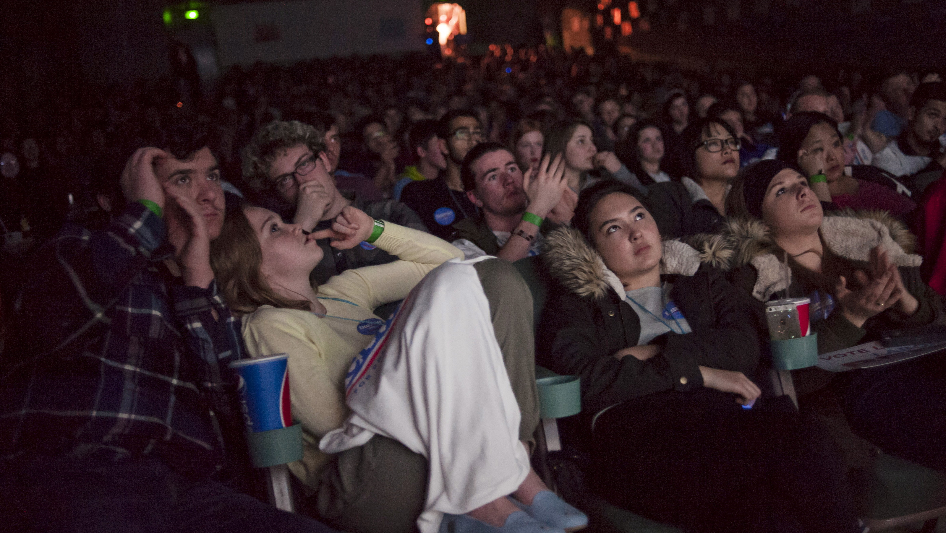 Andy Meyer (L), Maggie Timboe, Sasha Fetty and Mia Tiric watch the U.S. Democratic presidential candidates debate on a movie screen at a party event at a movie theatre in support of Democratic U.S. presidential candidate Bernie Sanders in Des Moines, Iowa November 14, 2015. REUTERS/Mark Kauzlarich - RTS740K