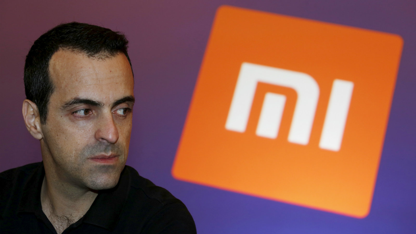 Xiaomi's Vice President Hugo Barra looks on in front of the company's logo during a group interview after the launching ceremony of Redmi Note 3 in Hong Kong, China March 21, 2016.