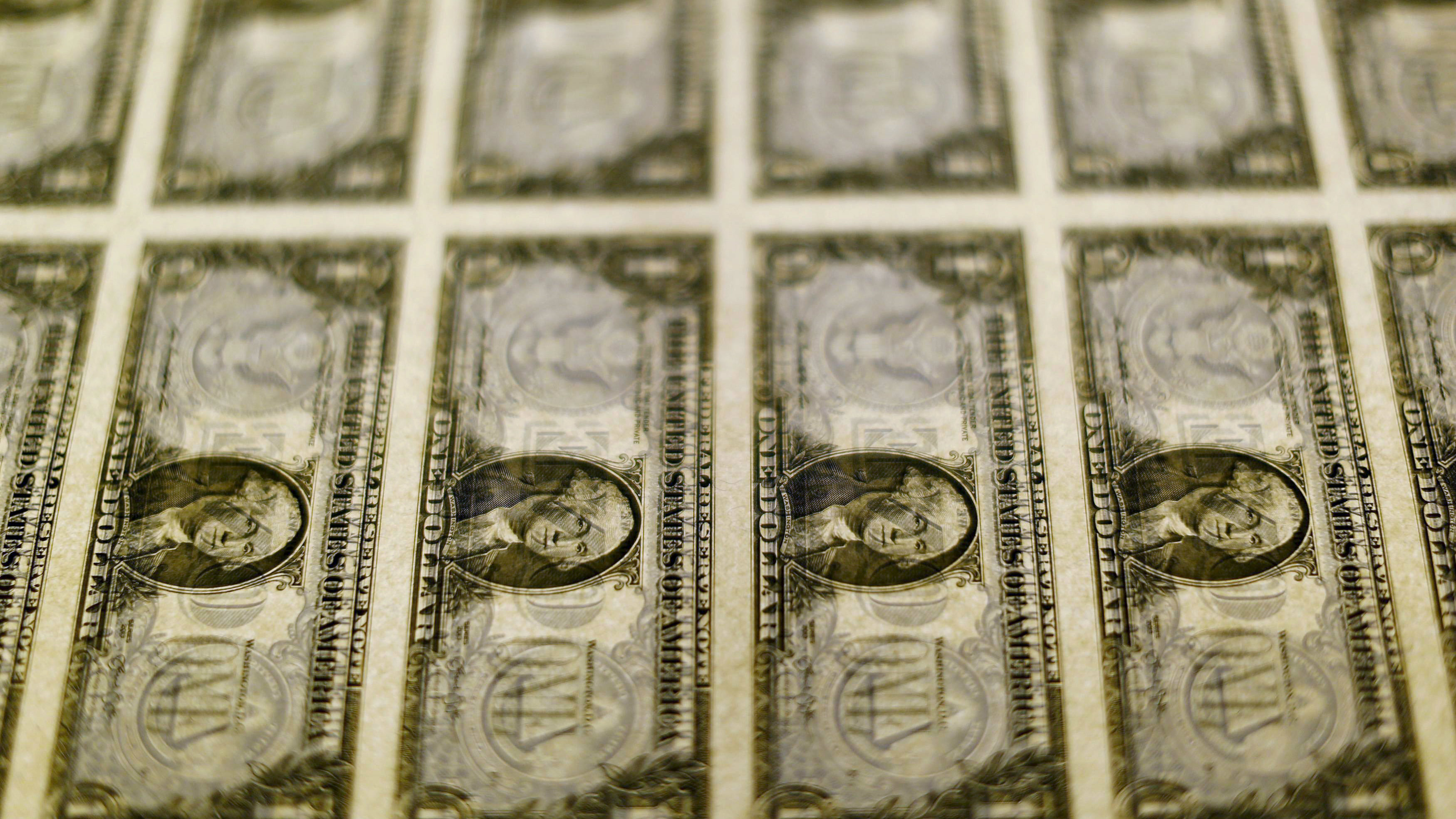 United States one dollar bills are seen on a light table at the Bureau of Engraving and Printing in Washington in this November 14, 2014, file photo.