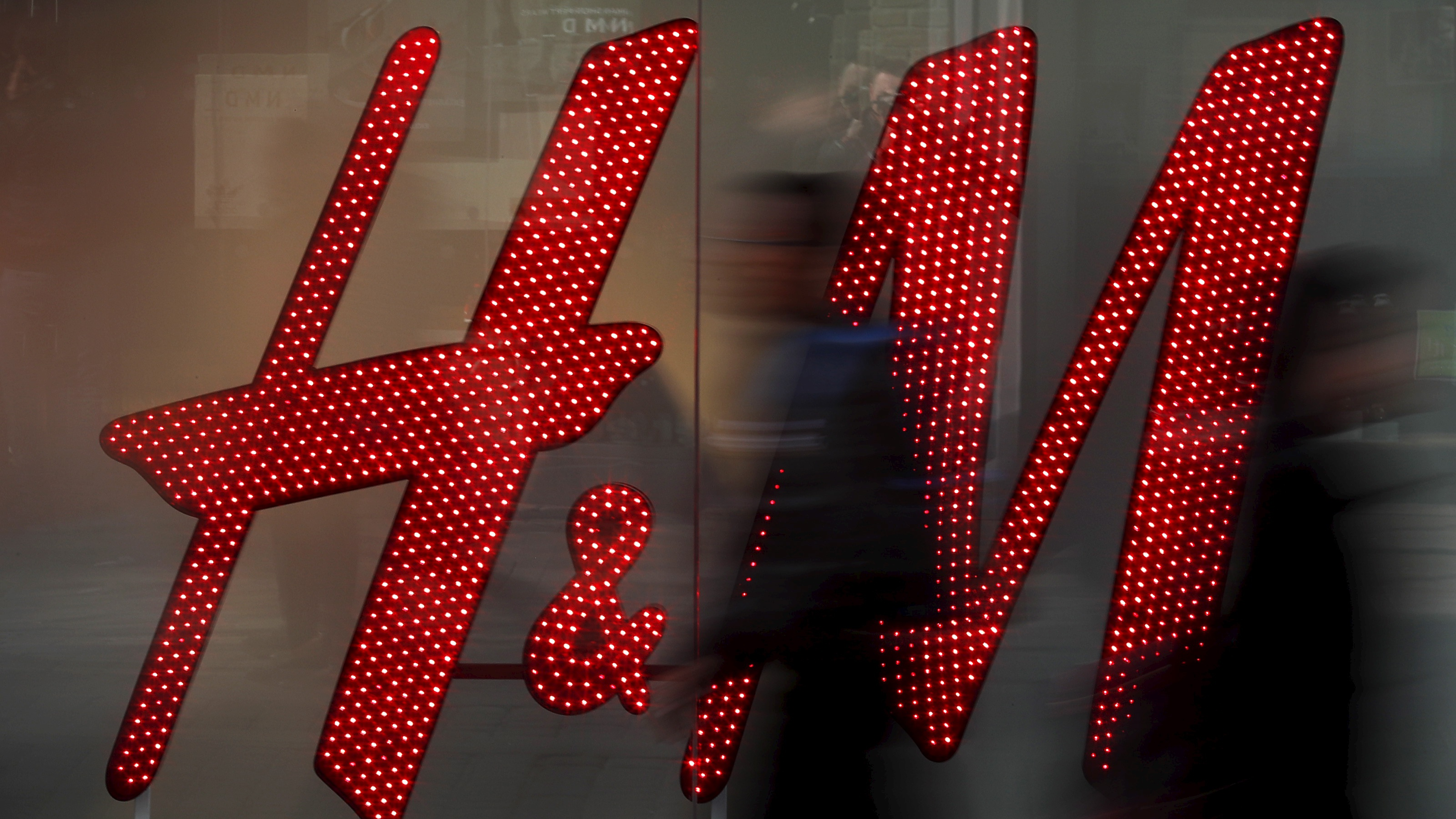 People walk past a company logo in the window of a H&M store in Manchester northern England, in this March 17, 2016 file photo.