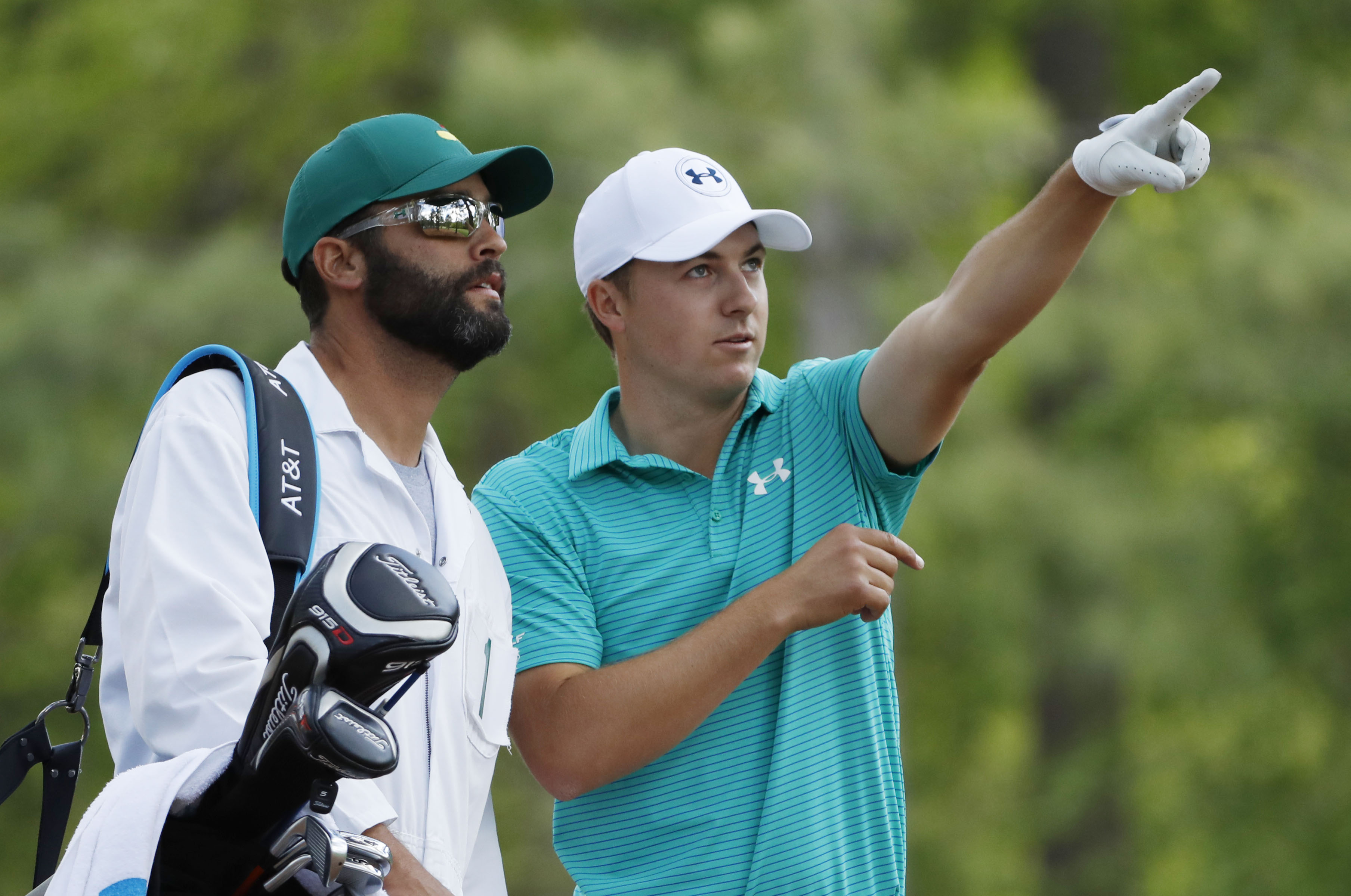 Jordan Spieth (right) gestures as he talks with caddie Michael Greller on the 11th hole during the first round of the 2016 The Masters golf tournament at Augusta National Golf Club.