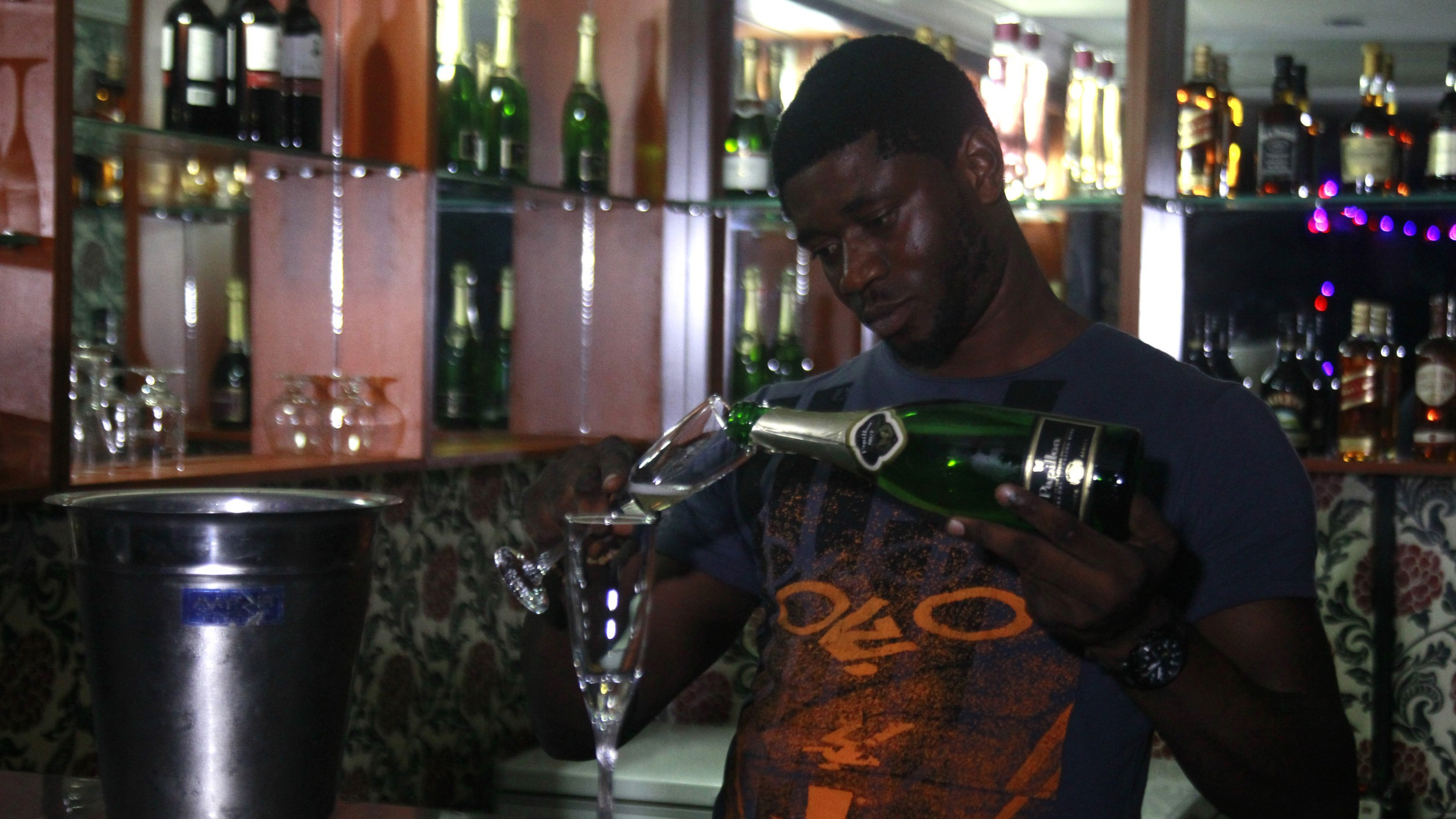 Peter Ode, 27, a mini-bar owner, serves champagne in his bar on McCarthy Street in Lagos June 12, 2013. Not so long ago, for luxury goods retailers the African market boiled down to a tiny elite, in some cases just a corrupt ruling clique. Not any more. Although millions of Africans remain stuck in crushing poverty, disposable incomes are on the up. As economies boom, the elite circles are widening and a growing middle class is aspiring to finer things. Picture taken June 12, 2013. REUTERS/Akintunde Akinleye (NIGERIA - Tags: BUSINESS) - RTX10NMB