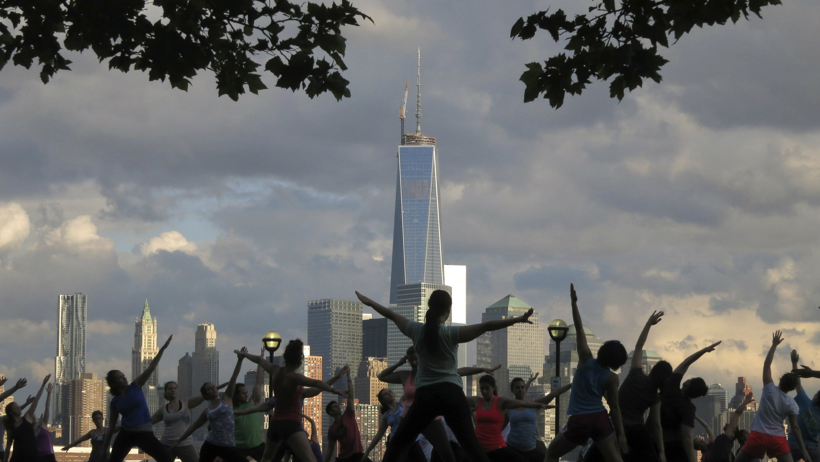 The Lower Manhattan skyline is seen in the distance during a weekly evening yoga class in a park along the Hudson River in Hoboken, New Jersey June 11, 2013.