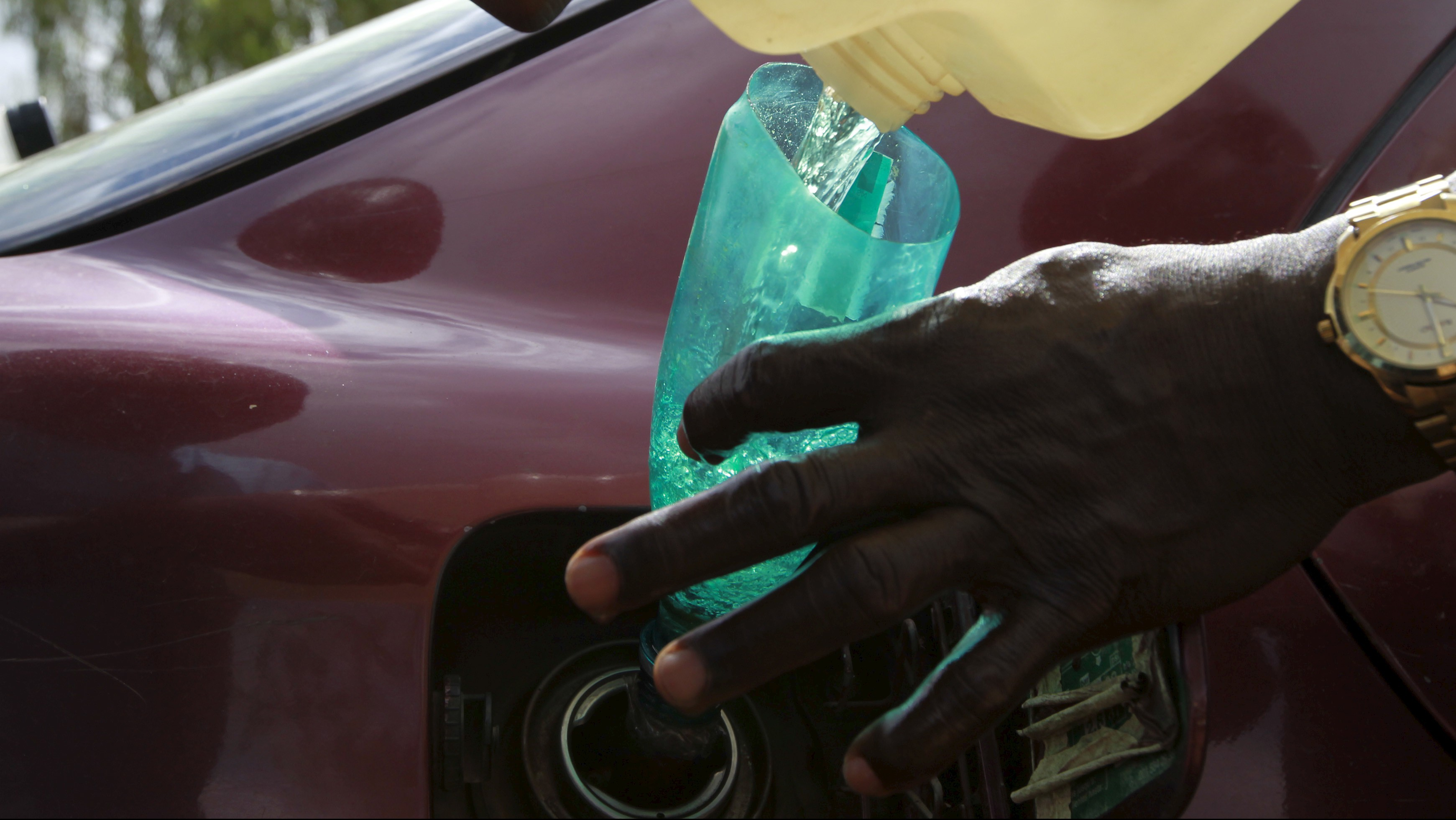A man pours petrol into a car tank outside the NNPC mega petrol station in Abuja, Nigeria May 25, 2015. REUTERS/Afolabi Sotunde - RTX1EGS2