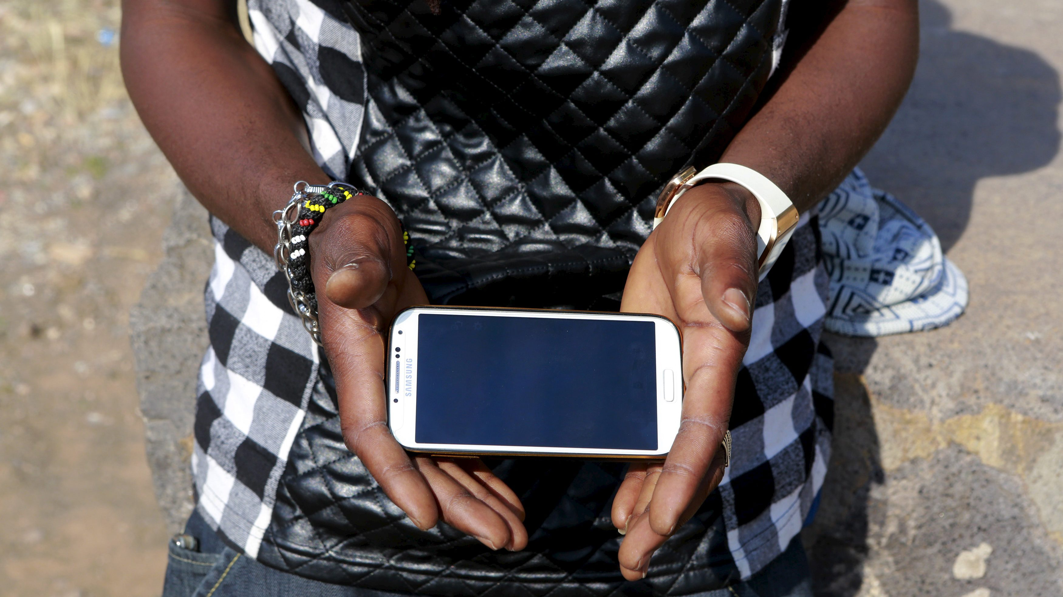 Said Youssef, 30, a rapper from Ghana, holds his mobile phone in the town of Oujda, northern Morocco, June 11, 2015. Youssef aims to cross the border into Spain's north African enclave of Melilla and realize his dream of becoming professional singer. REUTERS/Youssef Boudlal?     - RTX1H40S