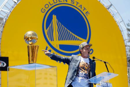 Jun 19, 2015; Oakland, CA, USA; Co-executive chairman and CEO Joe Lacob points towards the Larry O'Brien trophy during the Golden State Warriors 2015 championship celebration in downtown Oakland.