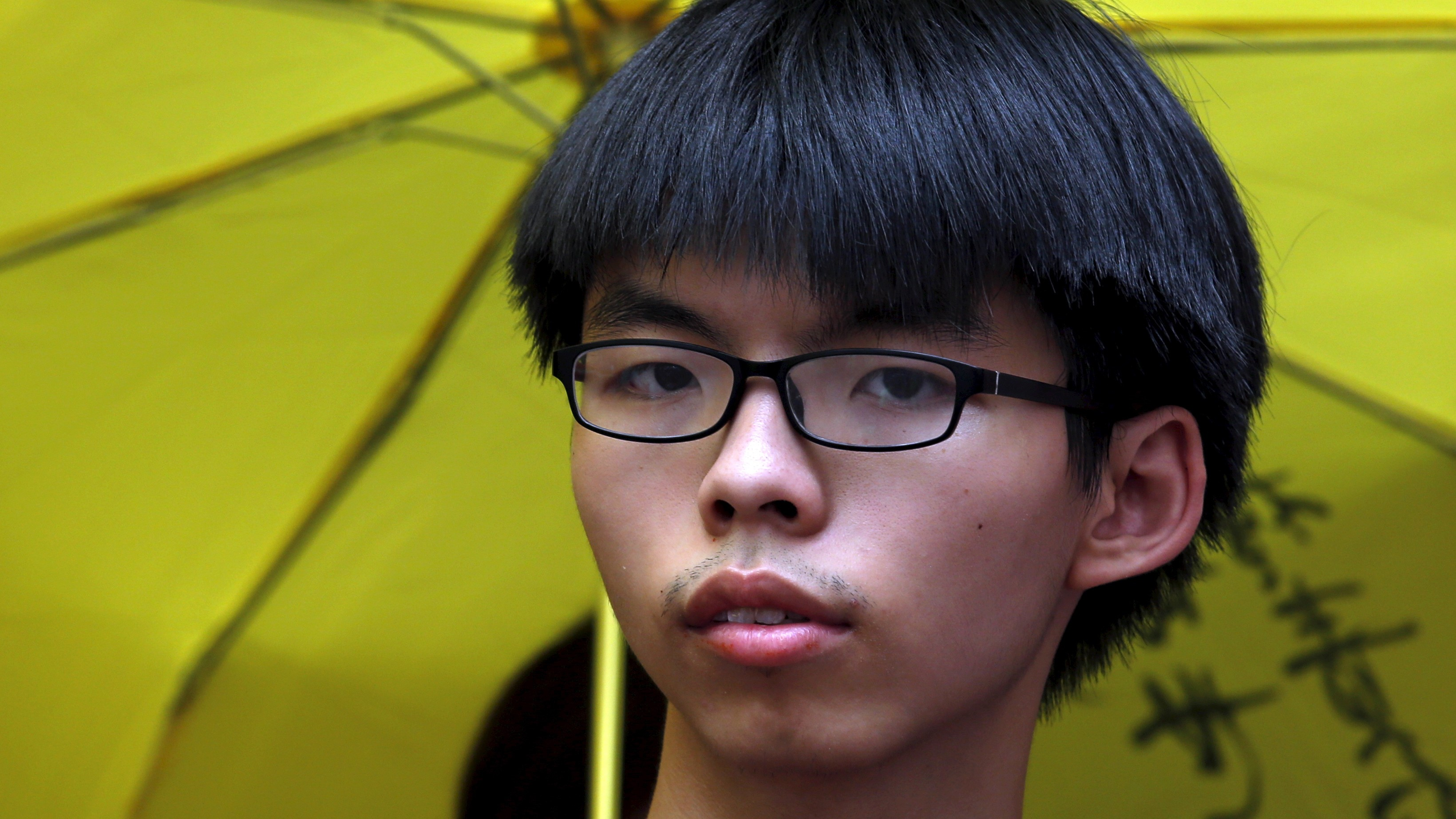 Student leader Joshua Wong stands in front of a supporter holding a yellow umbrella, symbol of the Occupy Central movement, outside a police station in Hong Kong, China July 14, 2015. Wong and another student leader Nathan Law reported to the police on Tuesday, expected to be charged with obstructing police officers during a protest outside China Liaison Office in 2014. REUTERS/Bobby Yip - RTX1K9JE