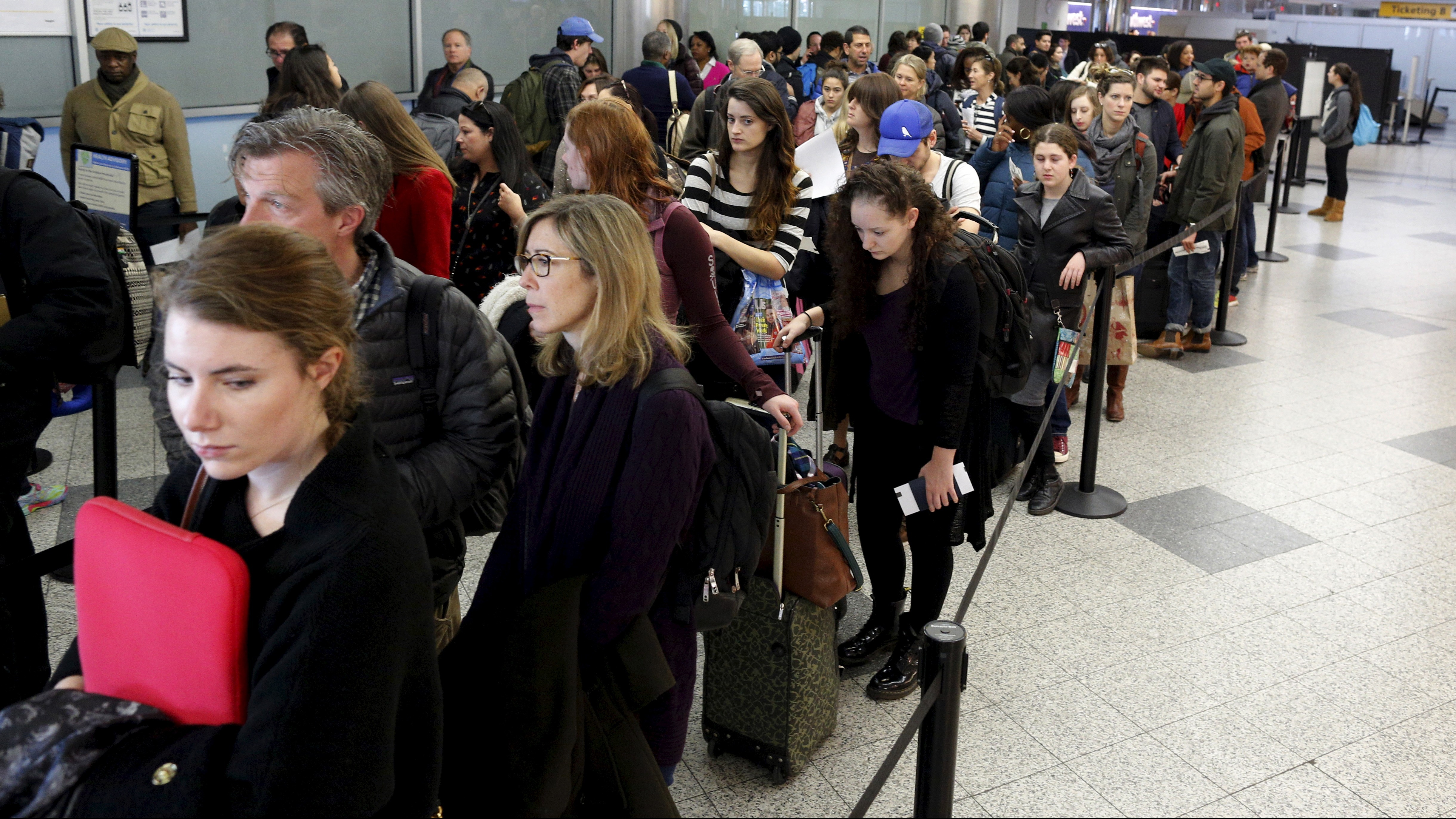 Travelers wait in line at a security checkpoint at La Guardia Airport in New York November 25, 2015. Millions of Americans embarked on their Thanksgiving travels on Wednesday with security in airports, at New York City's parade festivities, and other venues expected to be heightened amid jitters after the Paris attacks last week.
