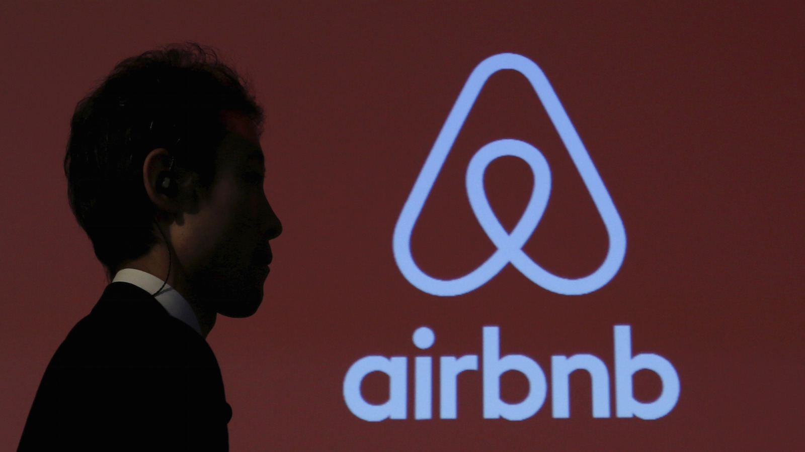 A man walks past a logo of Airbnb after a news conference in Tokyo, Japan, November 26, 2015.