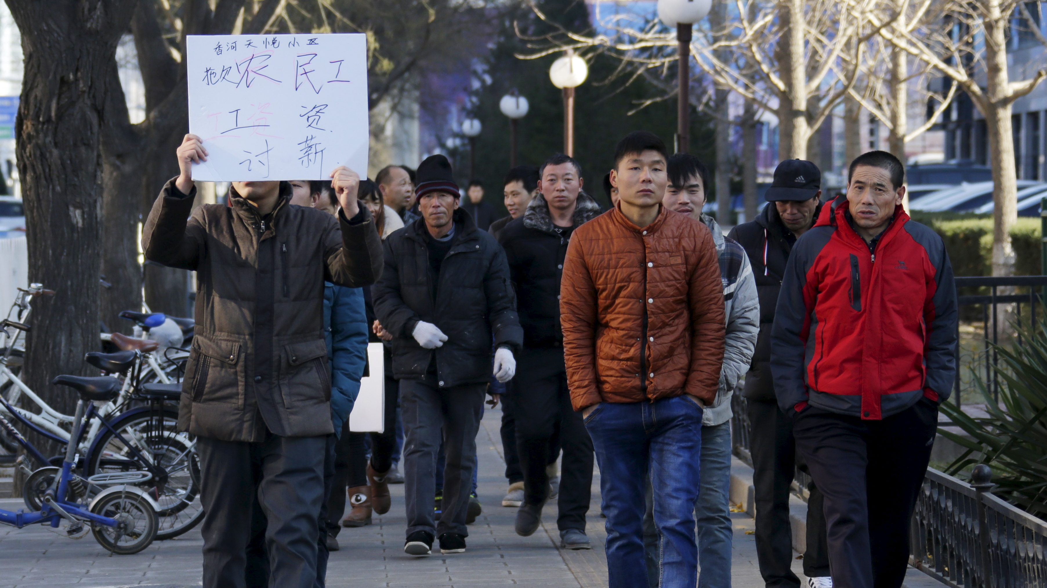 "Tian Honglei (L), a migrant worker from Henan province, holds a placard as he marches with his fellow workers along a main street to protest against a construction site and demand their salaries, in central Beijing, China, December 10, 2015. A total of 32 construction workers took to the street on Thursday to demand a construction site in Xianghe county of Hebei province to pay what they say are their delayed salaries worth about a total of 660,000 yuan (102,510 USD). The Chinese characters on the placard read, ""Delay migrant worker salary, demanding payments"". REUTERS/Jason Lee - RTX1Y0QA"