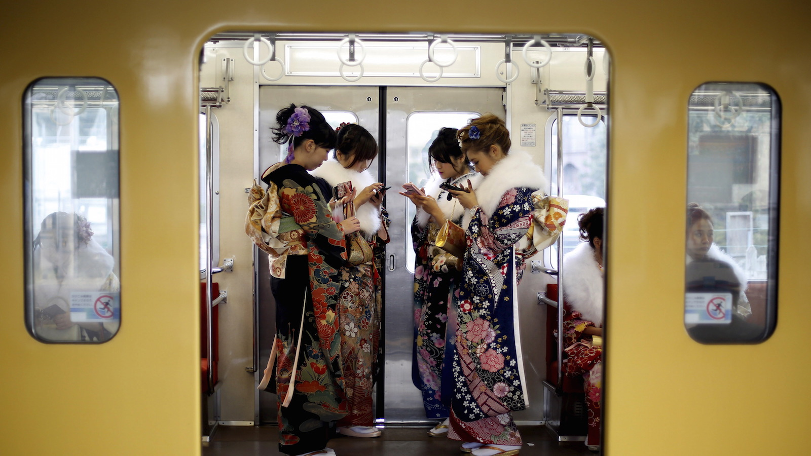 Japanese women wearing kimonos look at their mobile phones after their Coming of Age Day celebration ceremony at an amusement park in Tokyo January 11, 2016. According to a government announcement, more than 1.2 million men and women who were born in 1995 marked the coming of age this year, a decrease of approximately 50,000 from last year.