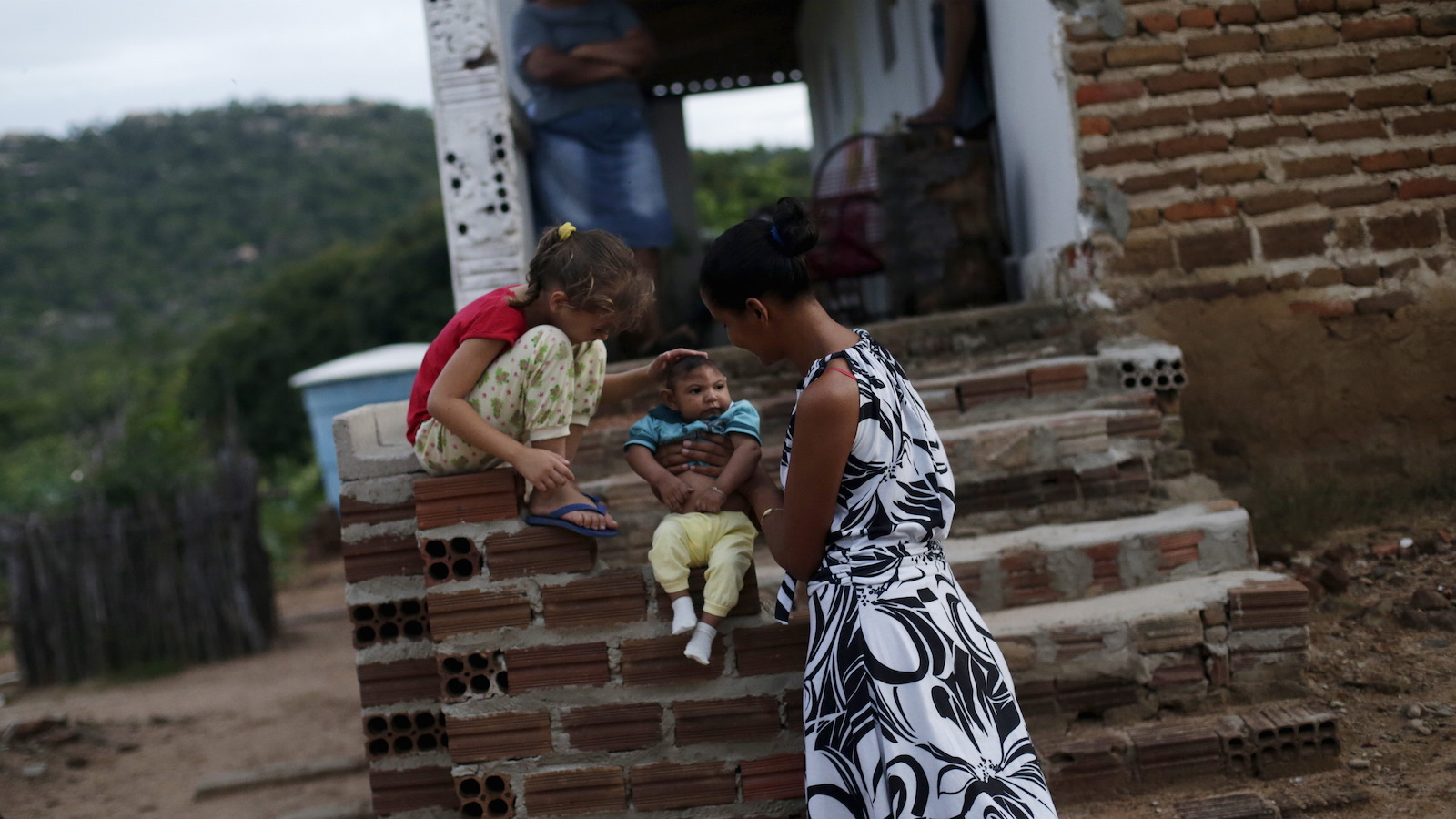Miriam Araujo, 25, holds Lucas, her 4-months old second child and born with microcephaly as her daughter Maisa, 6 caresses him, outside their house, in Sao Jose dos Cordeiros, Brazil , February 16, 2016.  Picture taken on February 16, 2016. REUTERS/Ricardo Moraes      TPX IMAGES OF THE DAY      - RTX287J2