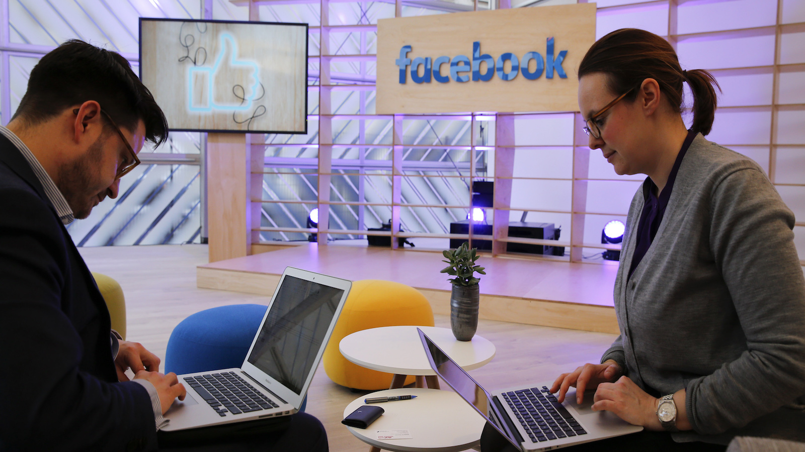 People work with their laptops in front of the Facebook logo at the new Facebook Innovation Hub during a preview media tour in Berlin, Germany, February 24, 2016.