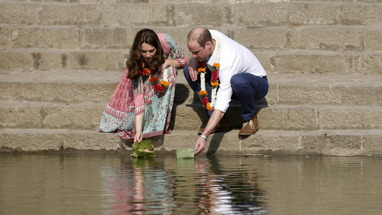 Britain's Prince William and his wife Catherine, Duchess of Cambridge, float flowers at the Banganga Water Tank in Mumbai, India, Sunday, April 10, 2016.